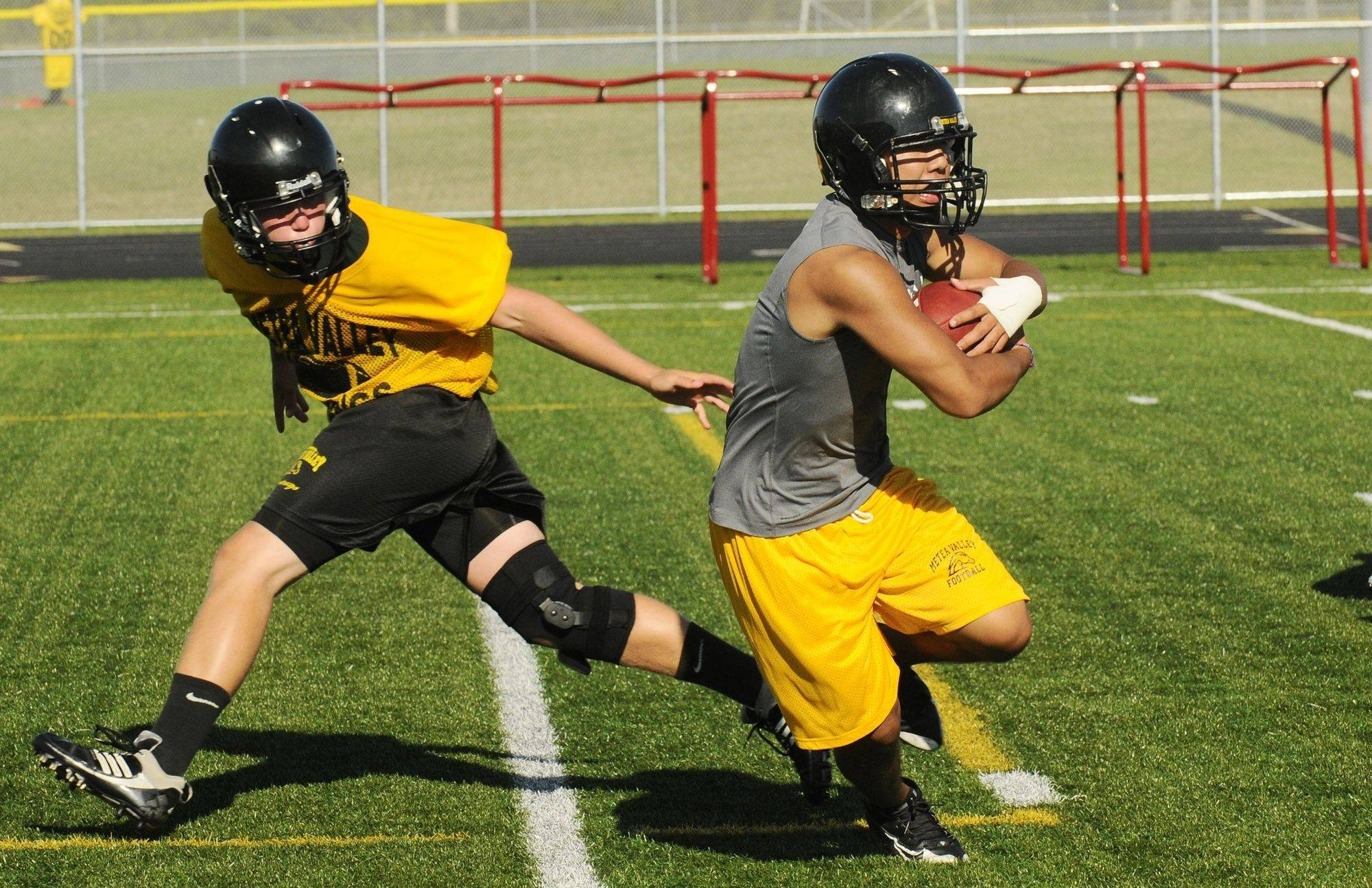Quarterback Jarrett House, left,hands the ball off to running back Sam Kim on the first day of practice for Matea Valley High School.