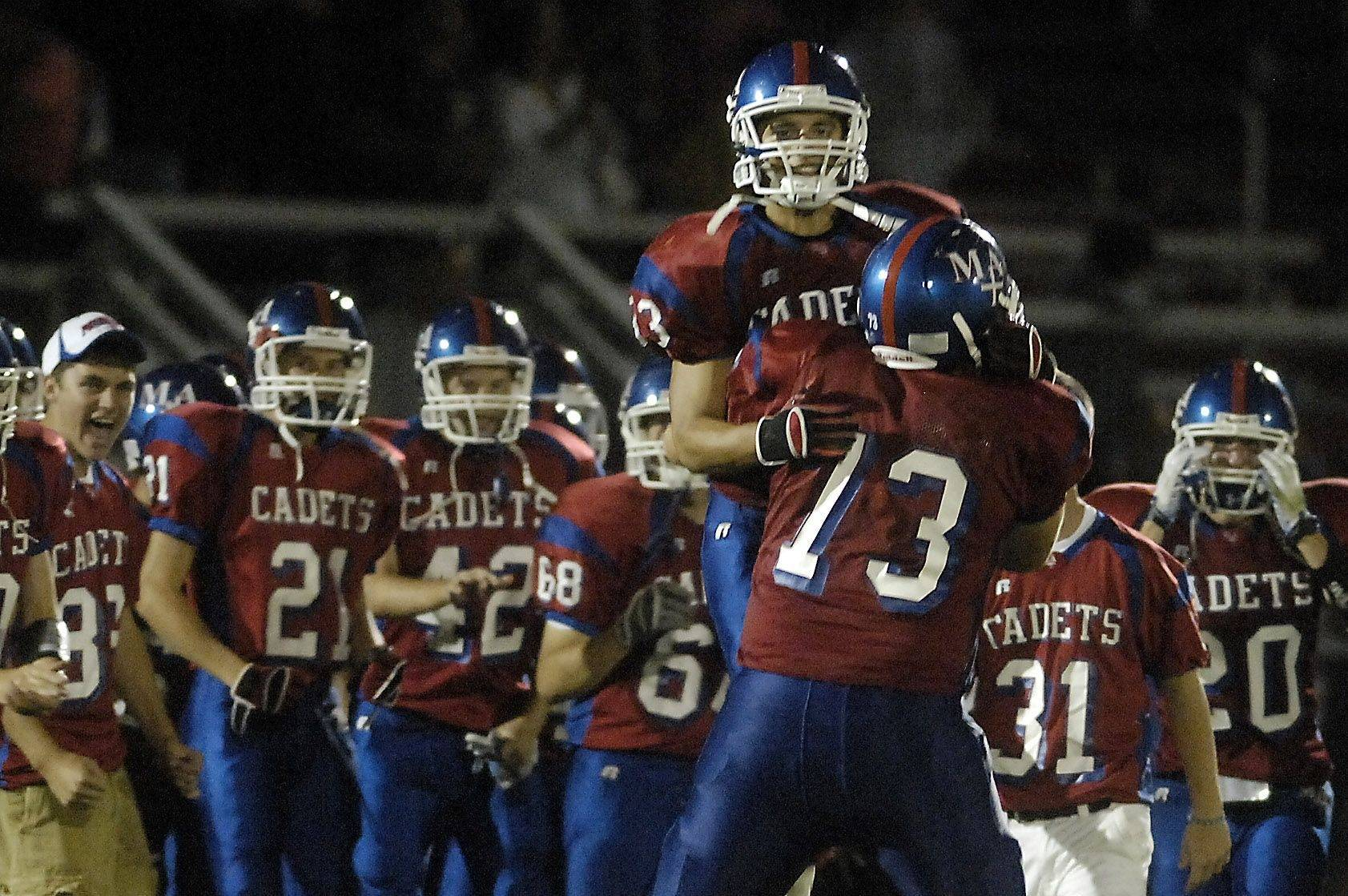 WEEK 1- Marmion's Garret Becker jumps into the arms of teammate Jake Winkel (73) following Friday's victory over Batavia at Marmion Academy in Aurora.