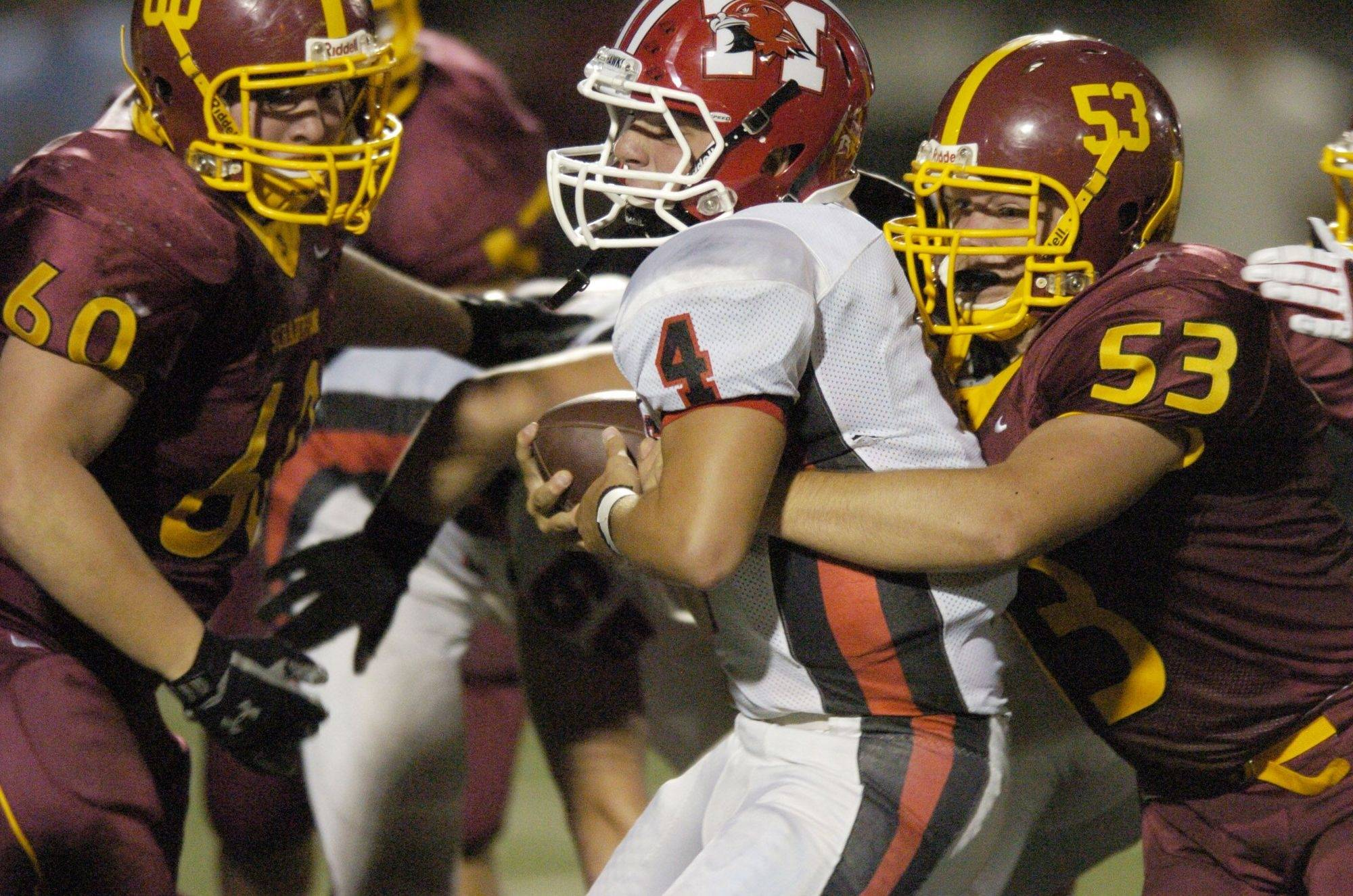 WEEK 1- Schaumburg's Don Wiencek, left, and Kyle Koburi, right, tackle Maine South's Jimmy Frankos.