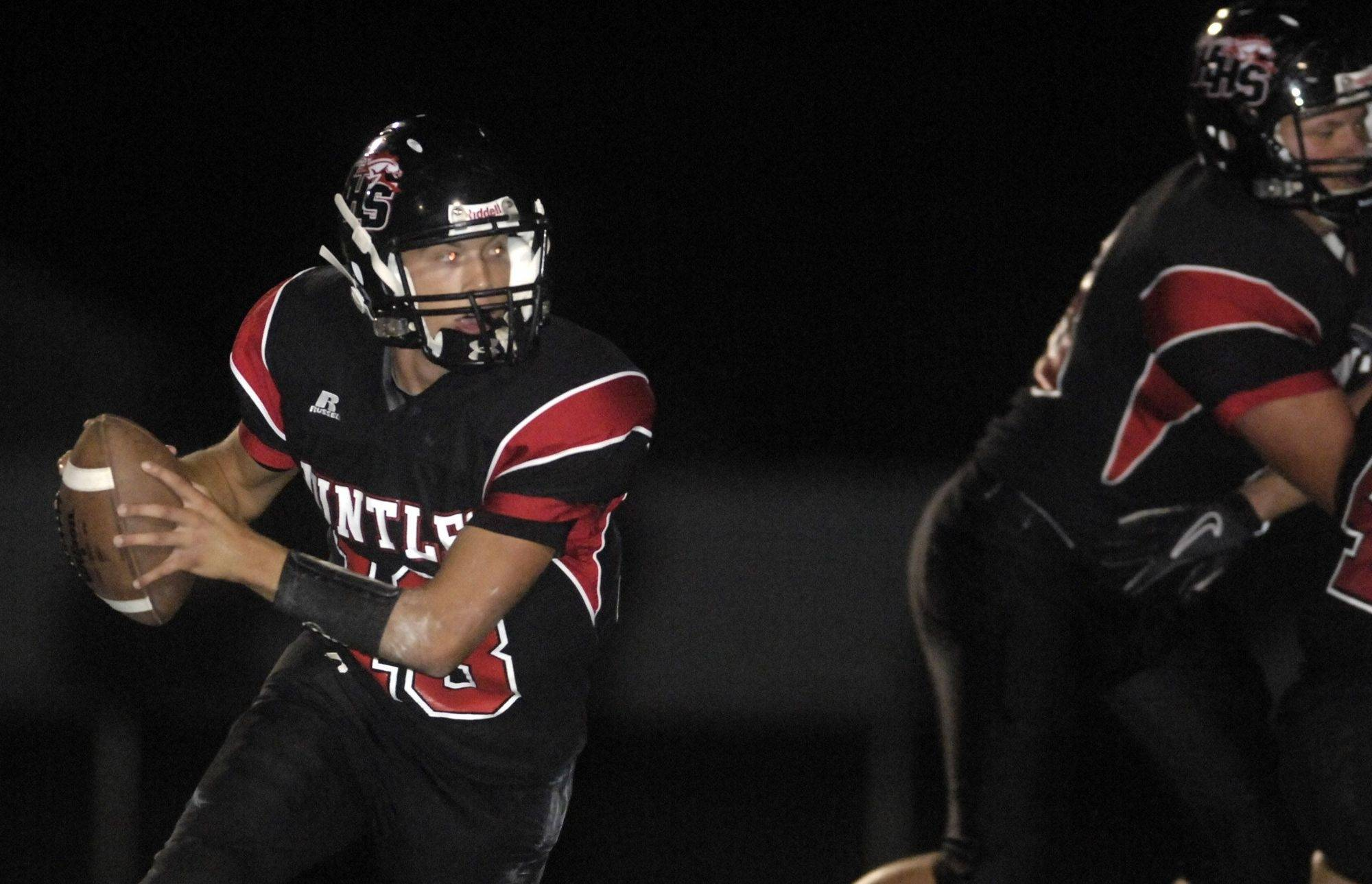 WEEK 2- Huntley quarterback Timothy Lycos rolls out to pass against Kaneland during Friday's game at Huntley.