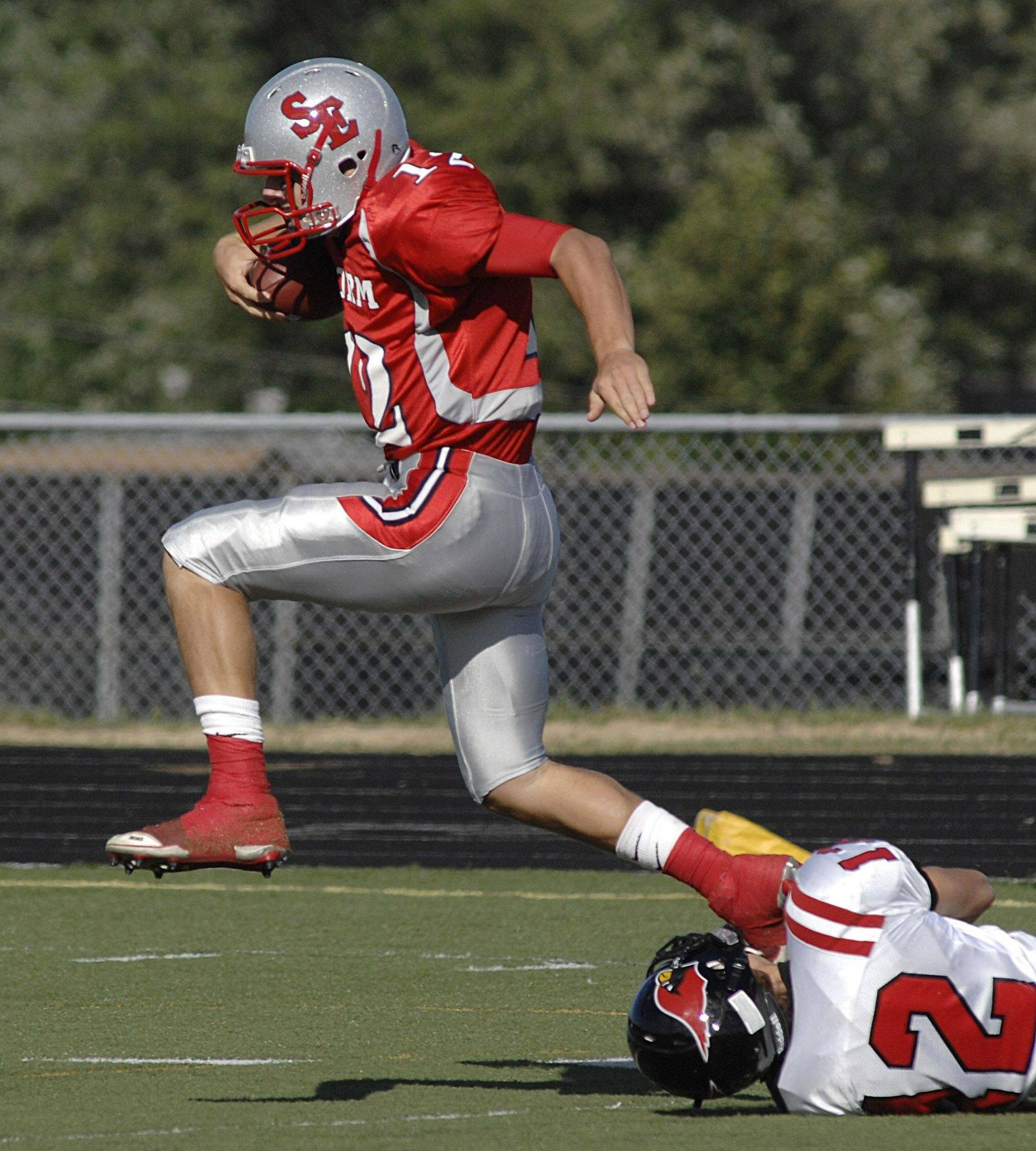 South Elgin's John Menken leaps out of the grasp of Metamora's Beau Geier to score a touchdown in the second quarter on Saturday, September 4.