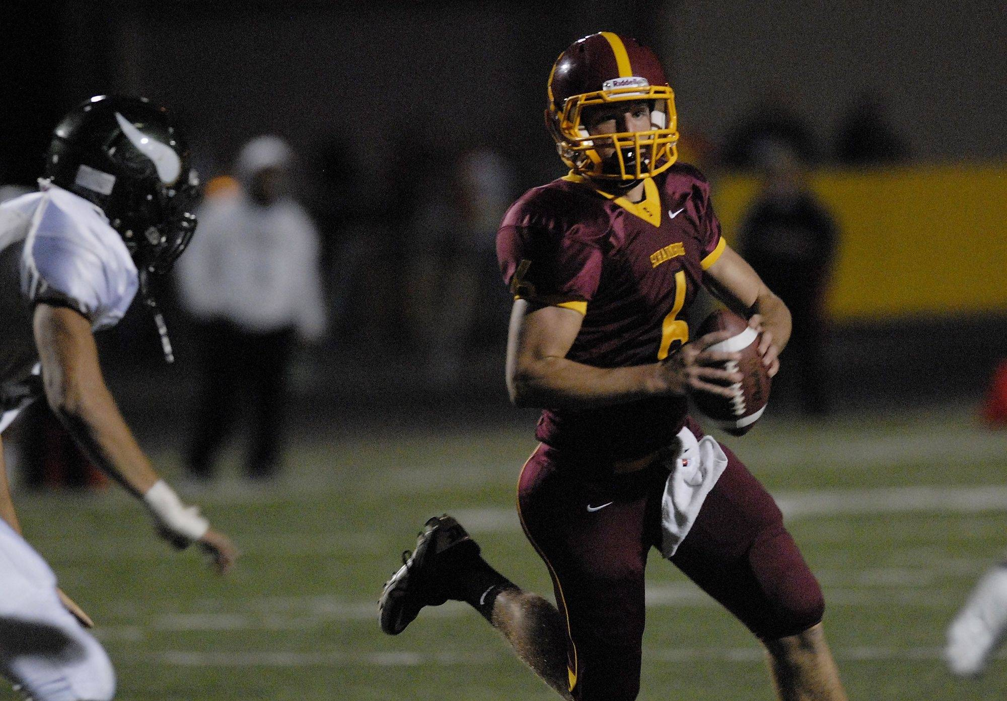 WEEK 5- Schaumburg's quarterback Mark Iannotti scrambles for a receiver but is hit by Fremd's Adam Mertes in the first quarter .