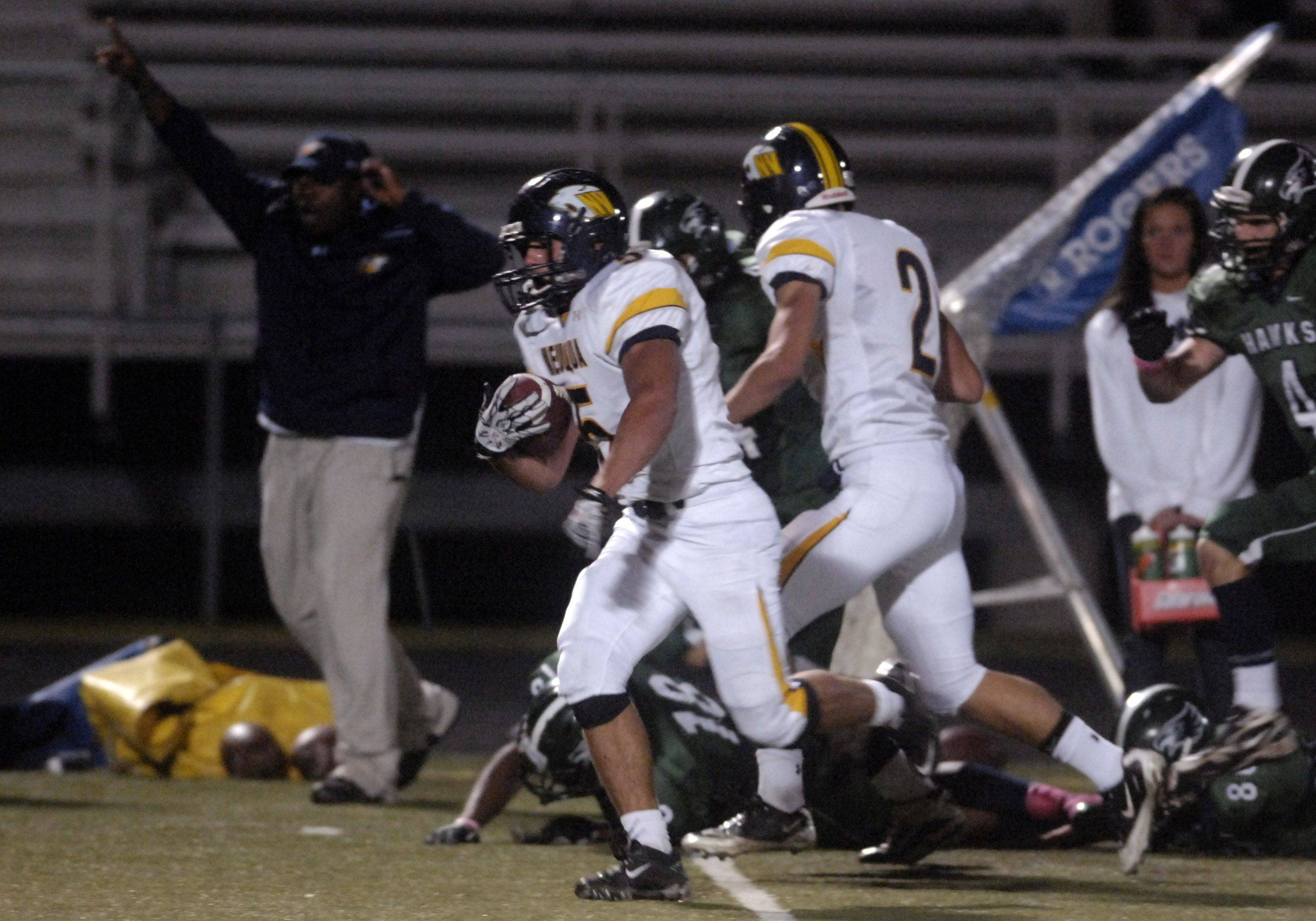 WEEK 8- Neuqua Valley's TJ Rhattigan leaves a bevy of broken tackles in his wake en route to a touchdown .