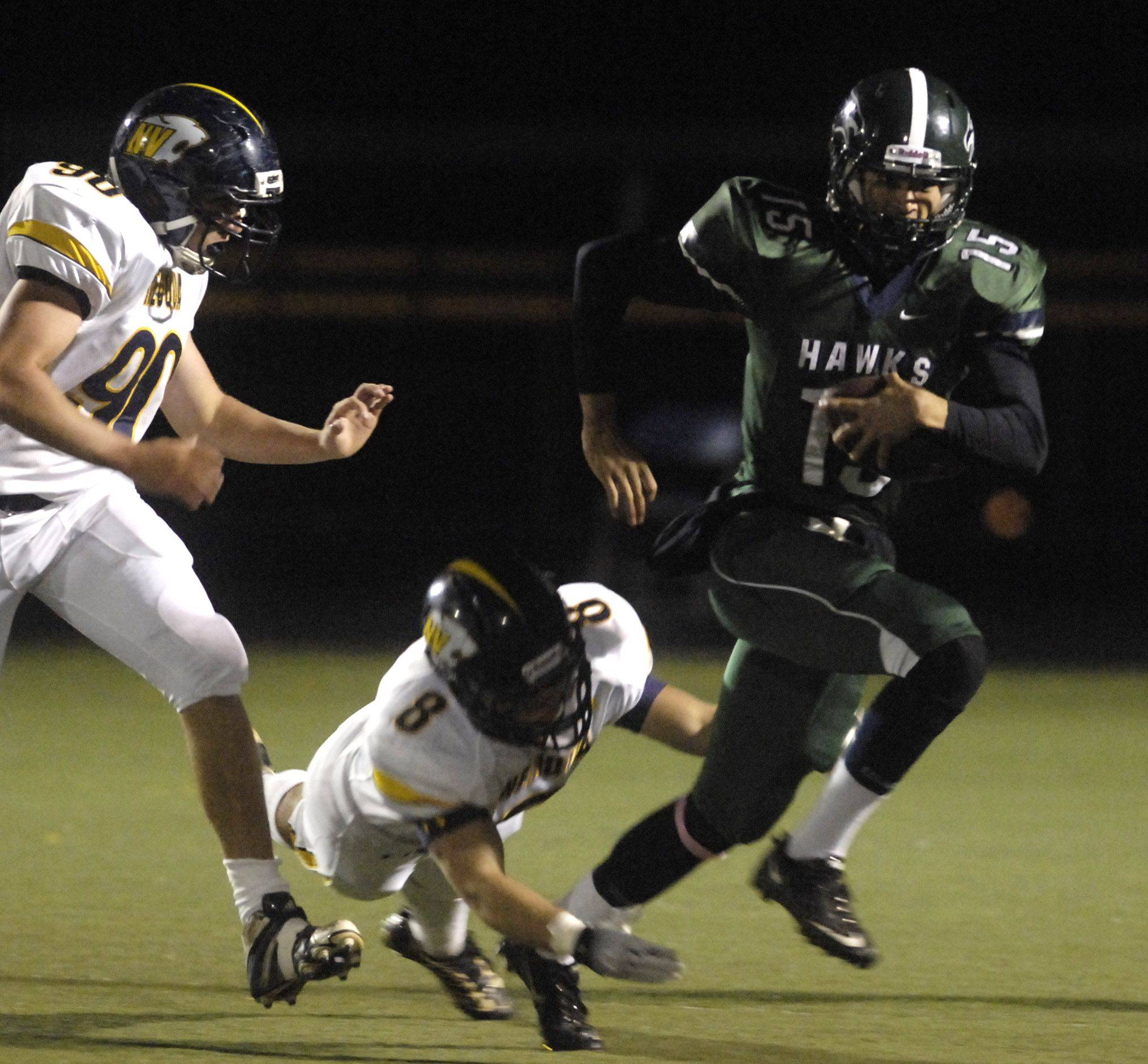 WEEK 8- Bartlett quarterback AJ Bilyeu escapes a diving tackle-attempt by Neuqua Valley's Austin Nance .
