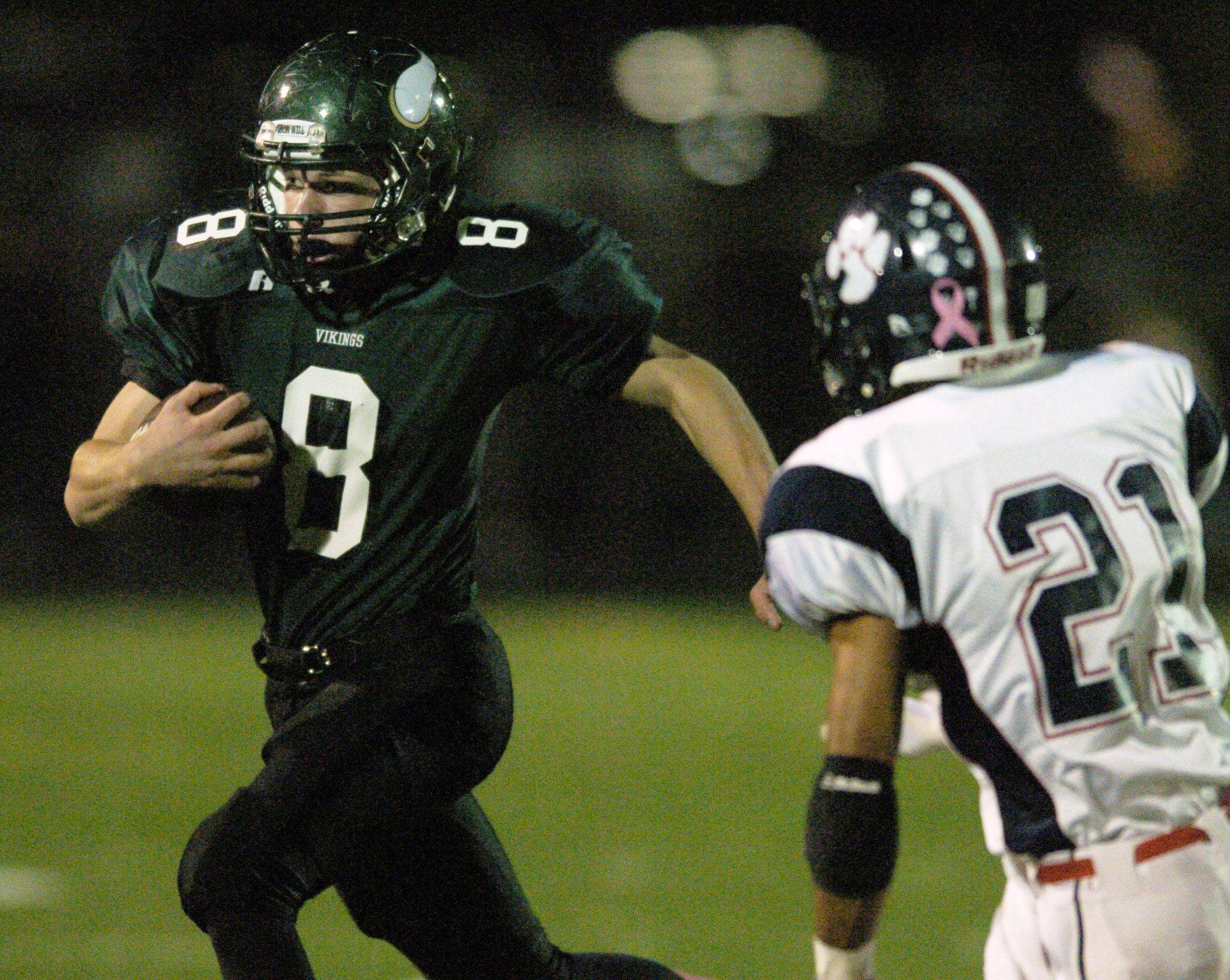 WEEK 9- Fremd quarterback Sam Beutler turns toward the sideline as Conant's London Dokubo closes in.