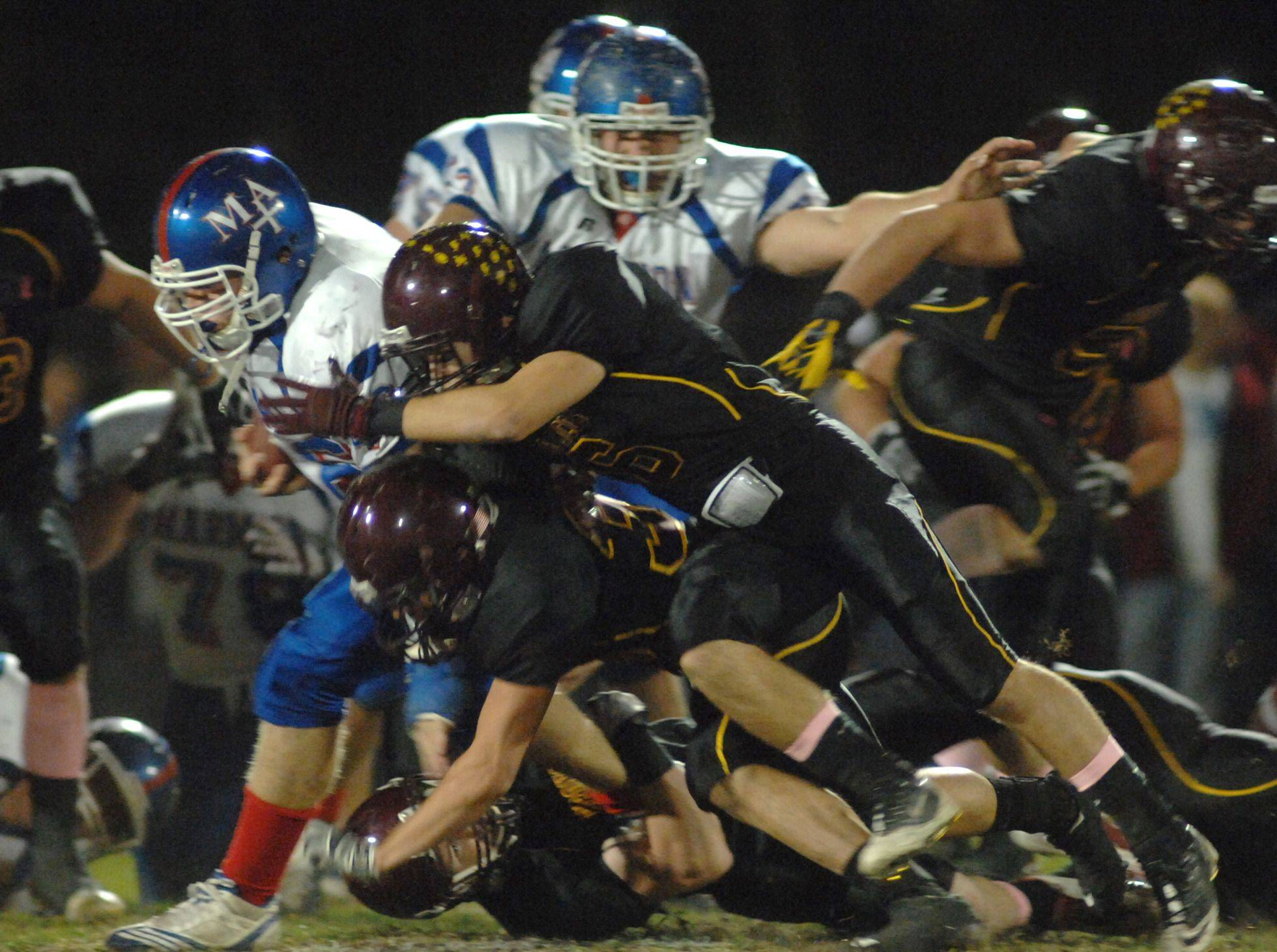 WEEK 9- Marmion Academy's T.J. Lally is taken down by Montini defenders.