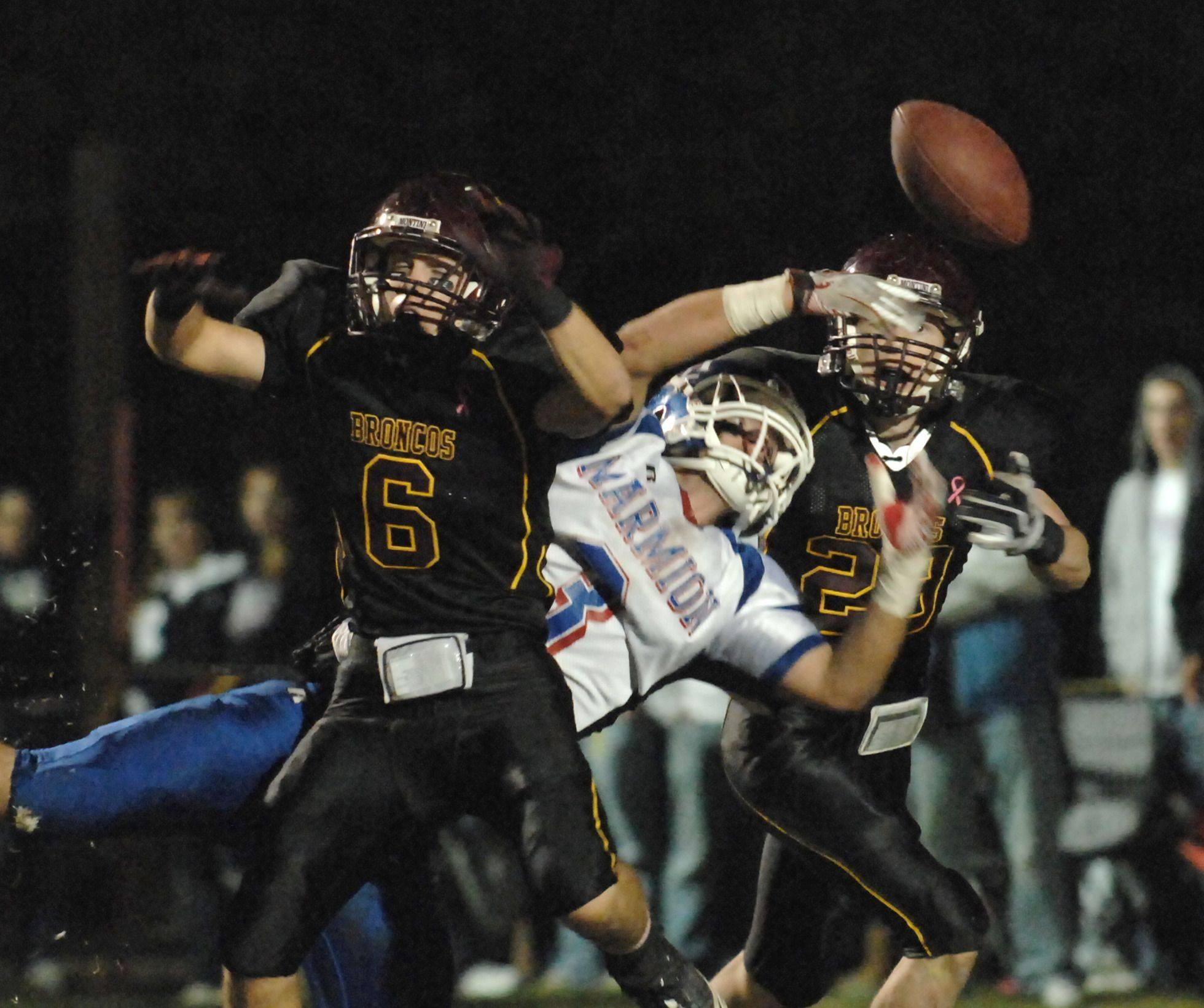 WEEK 9- Montini's Tom Desmond, left, and Connor Gorrell break up a pass intended for Marmion Academy's Nick Scoliere .