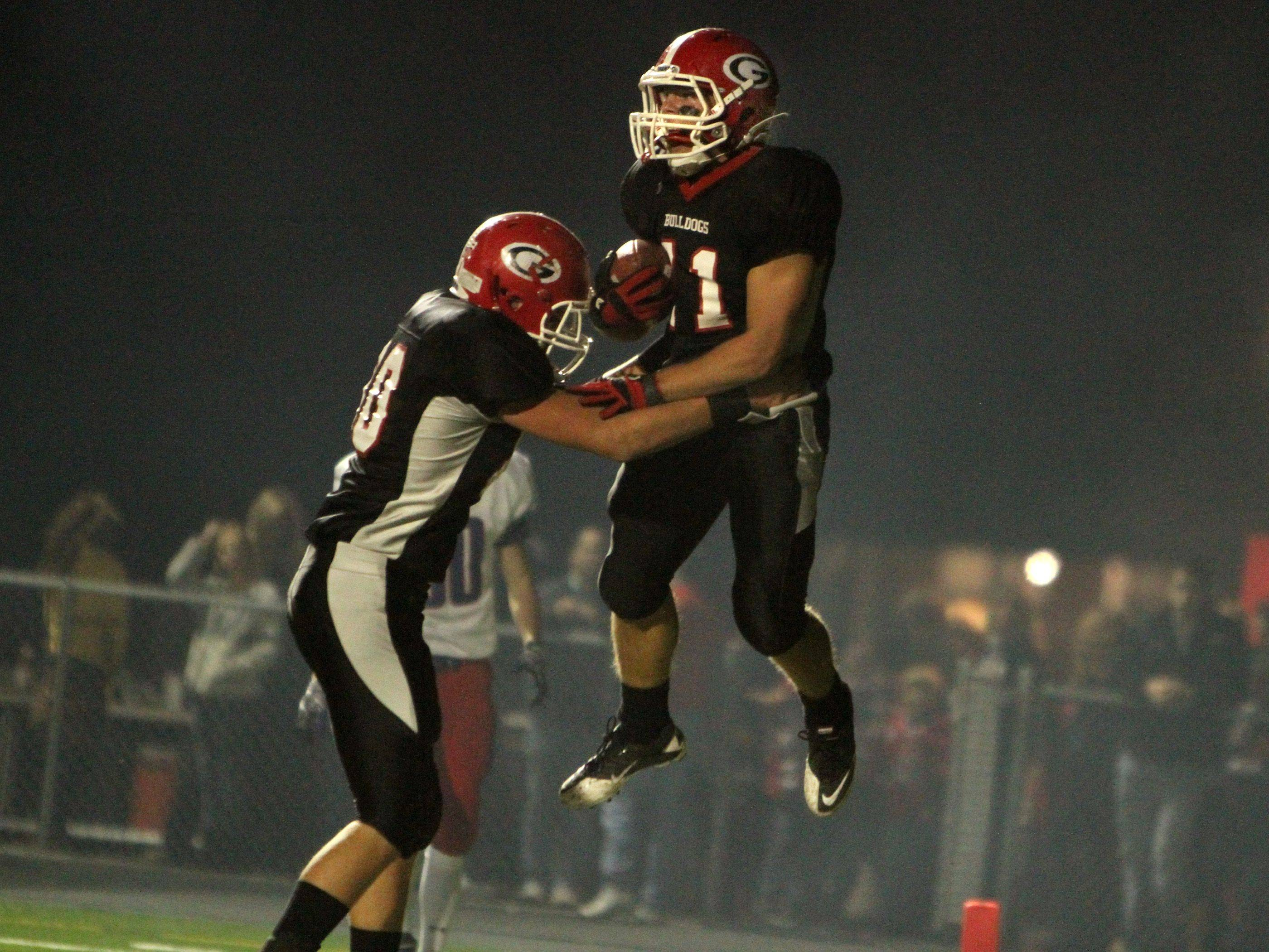 WEEK 9- Grant's Steven Niewiedzial leaps up, with the help of teammate Chris Orc, after scoring a touchdown against Lakes in the first quarter.