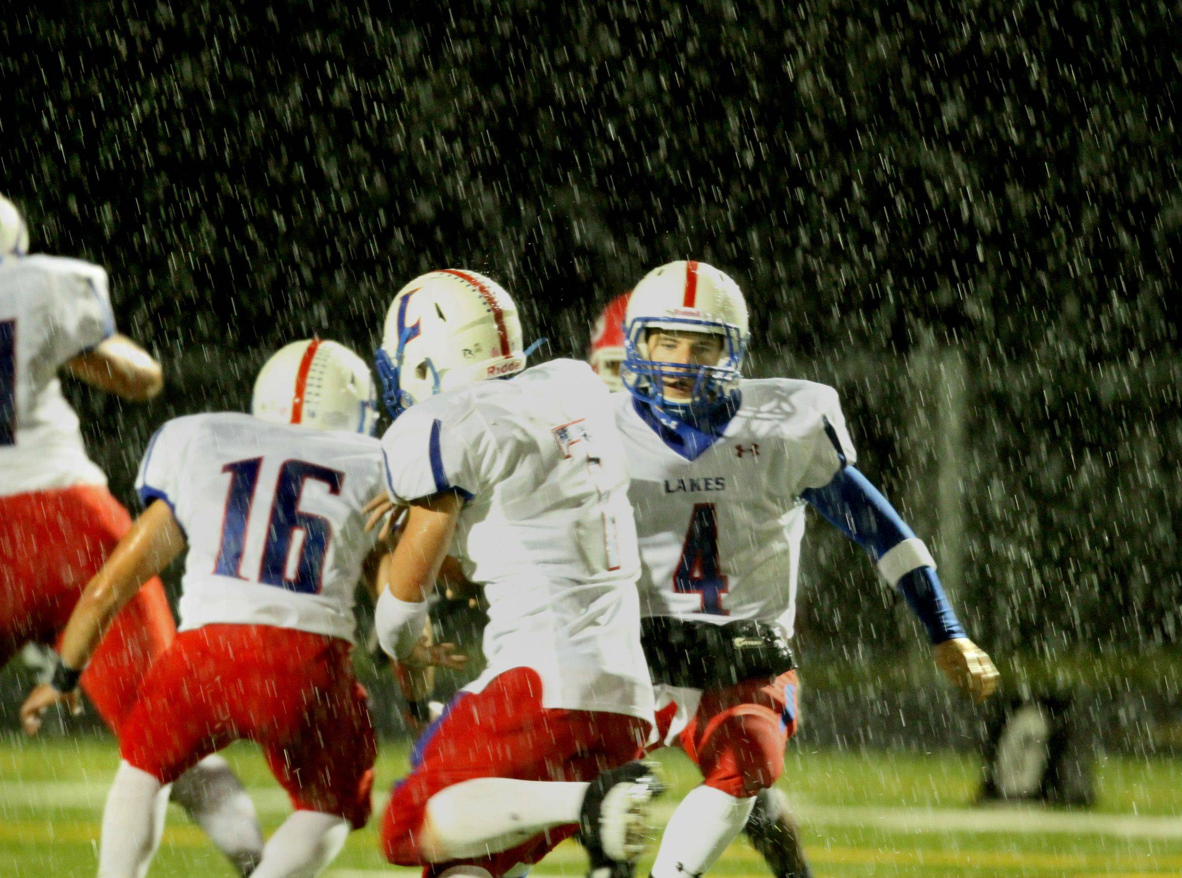 WEEK 9- Lakes quarterback Jeff Eder looks to hand the ball off against Grant as heavy rain falls in the second quarter.