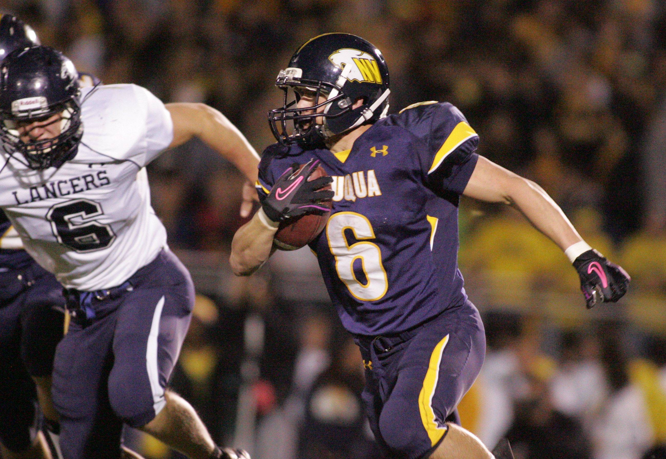 WEEK 9- Neuqua valley's Trent Snyder rushes past Lake Park players.