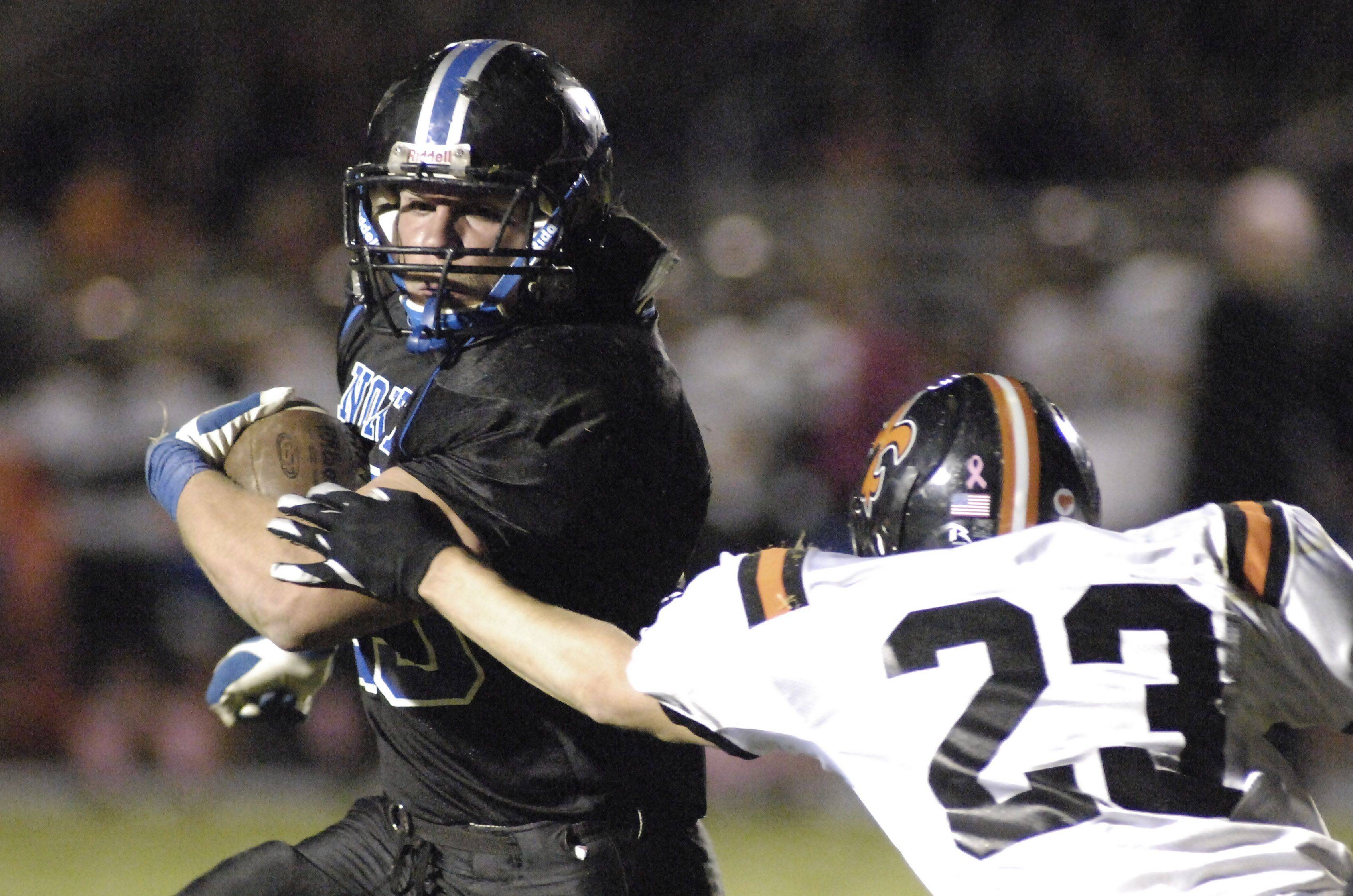 WEEK 9- St. Charles North's Dirk Schmitt shakes off St. Charles East's Carter Reading in the third quarter .