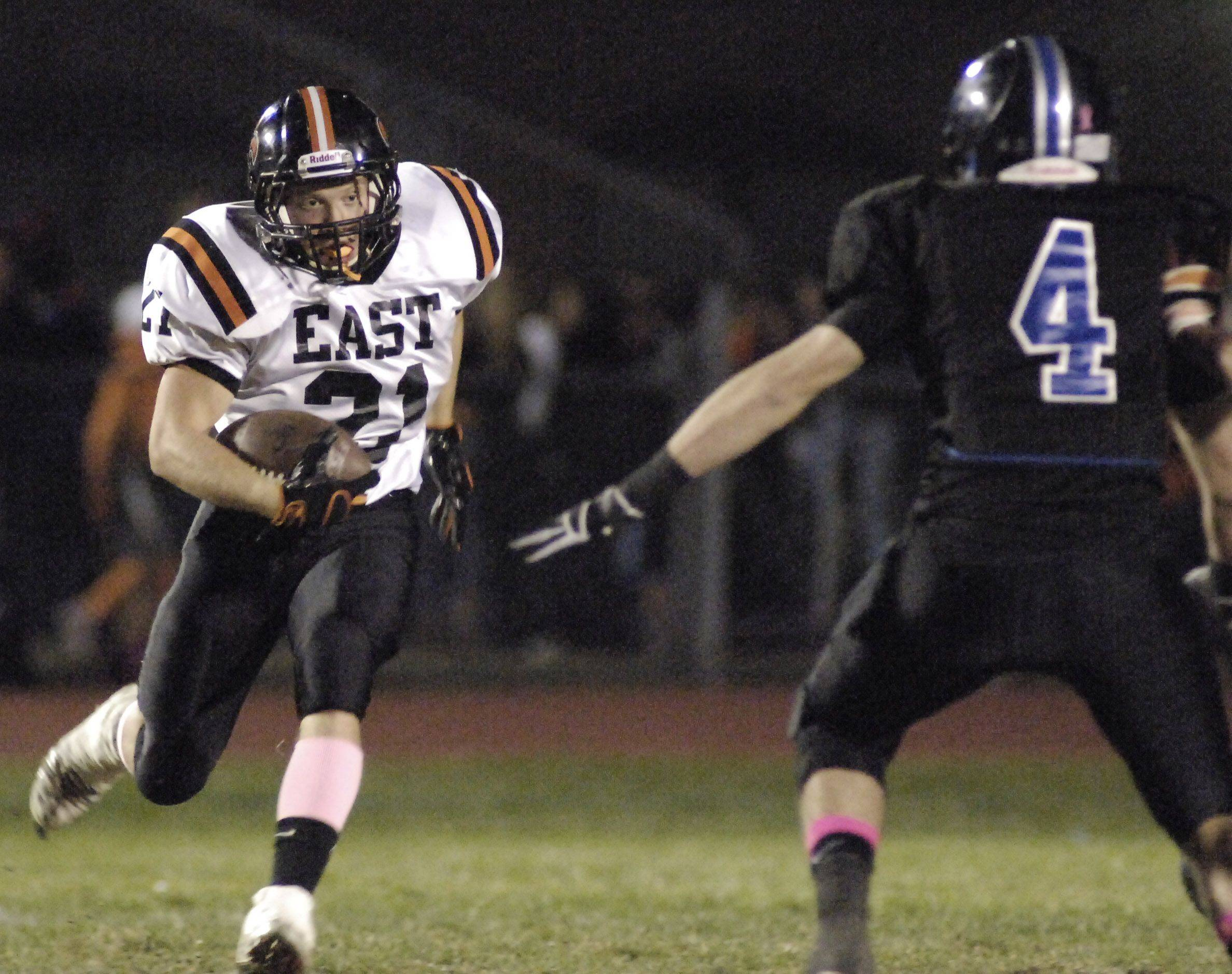 WEEK 9- St. Charles East's Zach Zajicek manuevers around St. Charles North's Patrick McGushin in the first quarter .