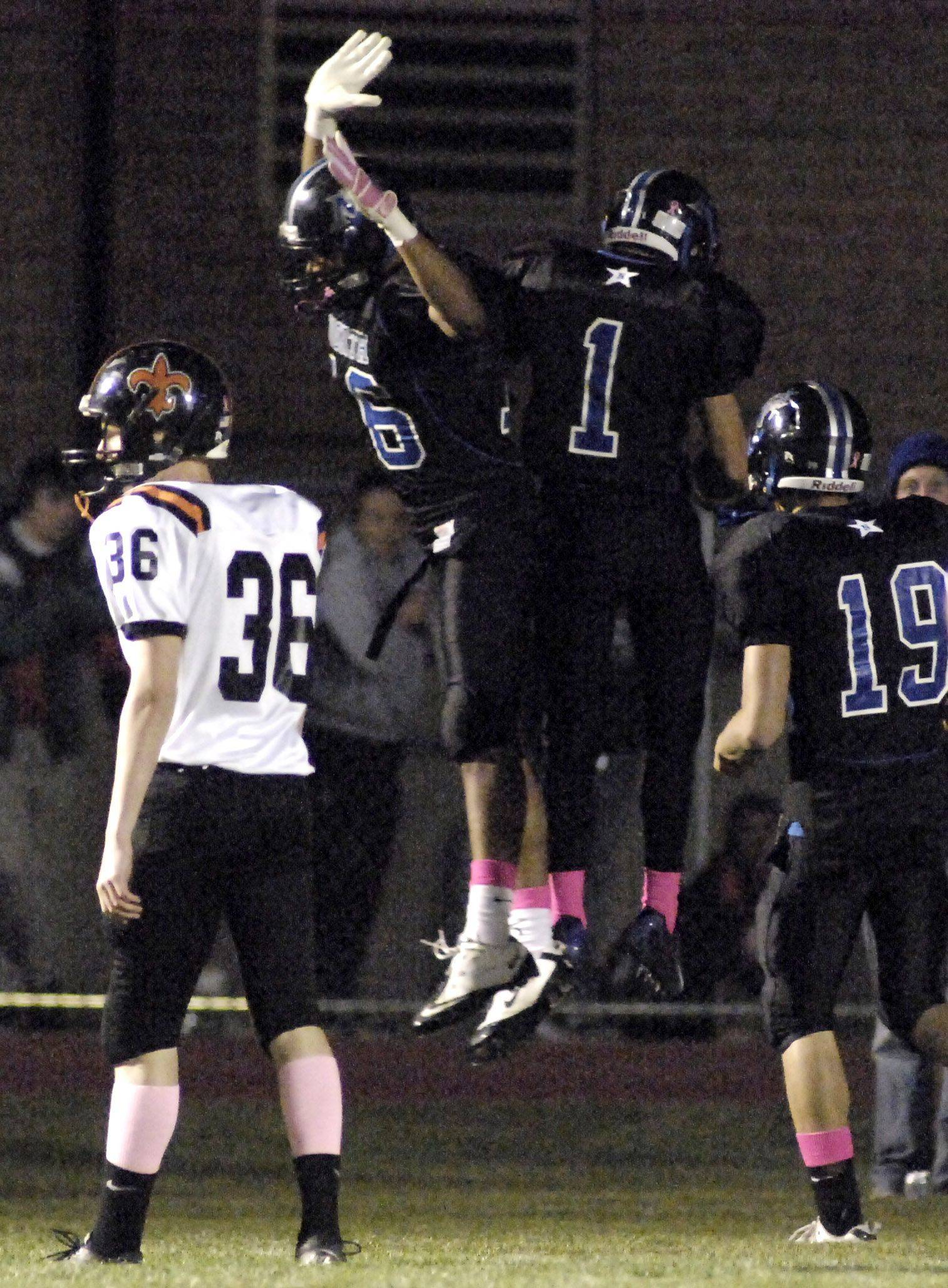 WEEK 9- St. Charles North's Josh Mikes and Andrew Elliott celebrate Elliott's touchdown in the third quarter .
