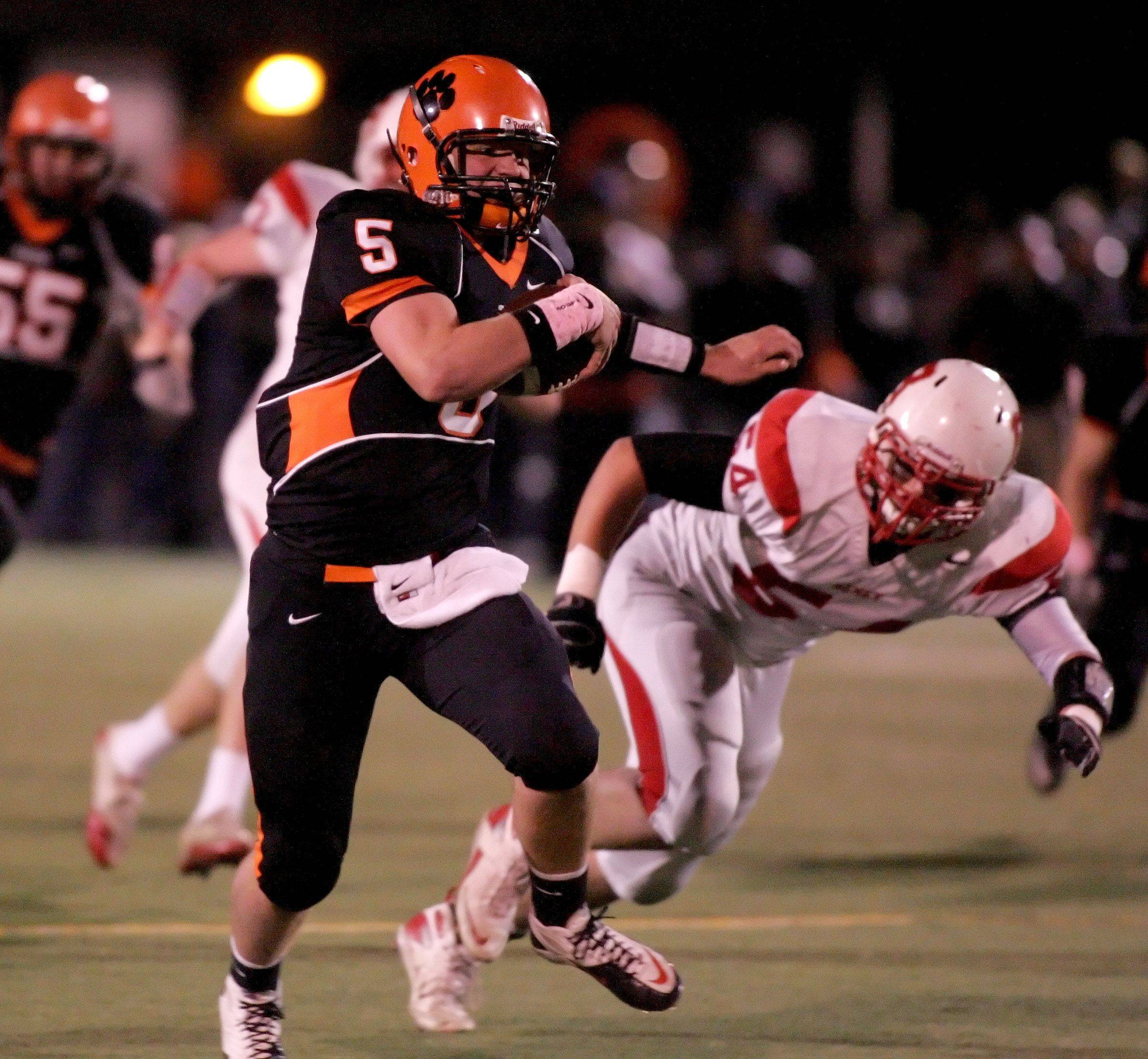 Wheaton Warrenville South quarterback Reilly O'Toole eludes Jeff Schmittgens, right of Benet during playoff football Friday in Wheaton.