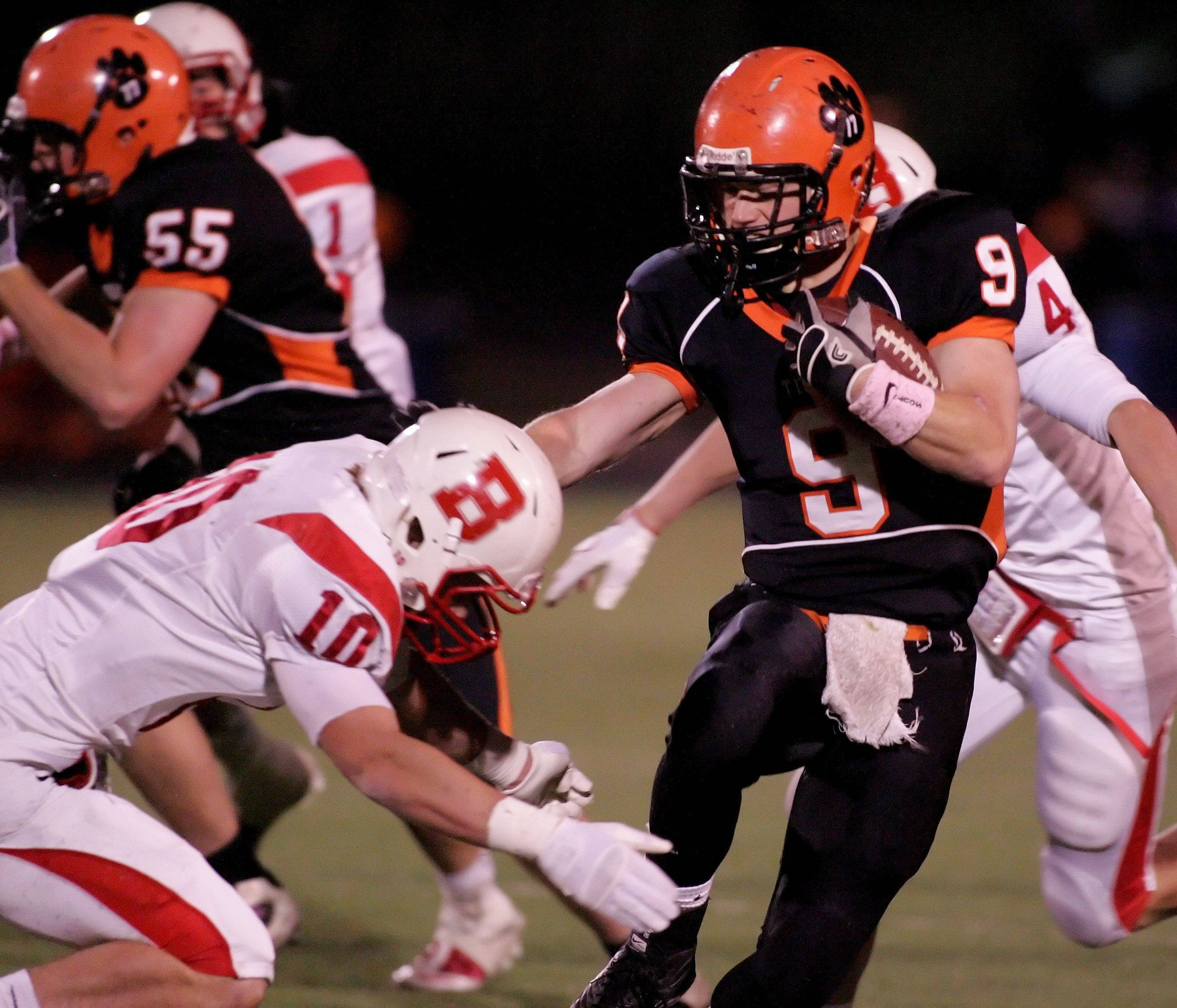 Nelligan Connor, left of Benet, moves in to tackle Matt Rogers of Wheaton Warrenville South, right, during playoff football Friday in Wheaton.