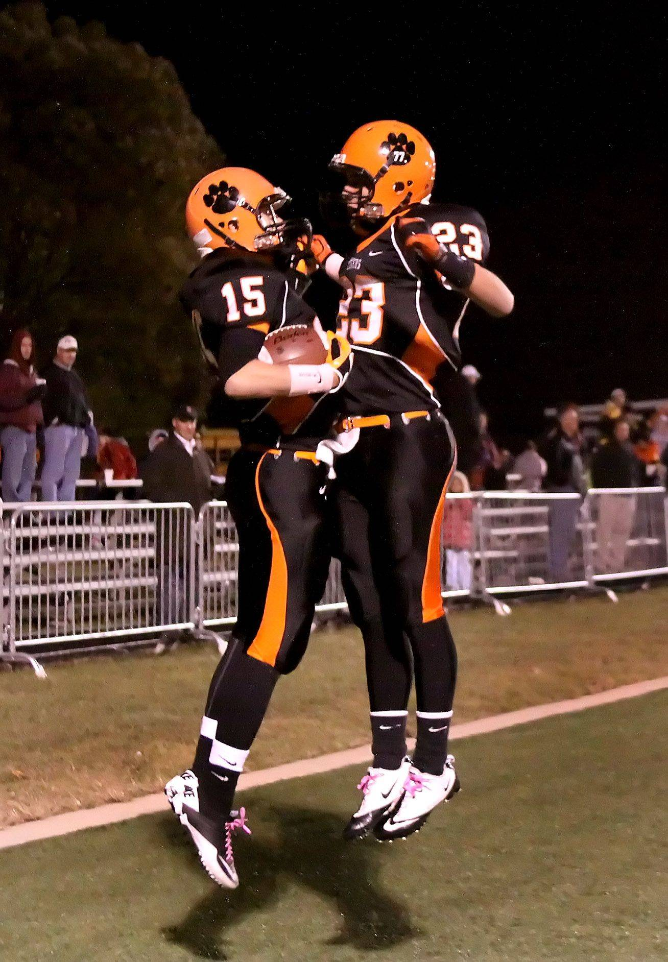 Travis Kern, right, jumps up to celebrate a touchdown by Ryan Crowe, left of Wheaton Warrenville South during their win over Benet in playoff football Friday in Wheaton.