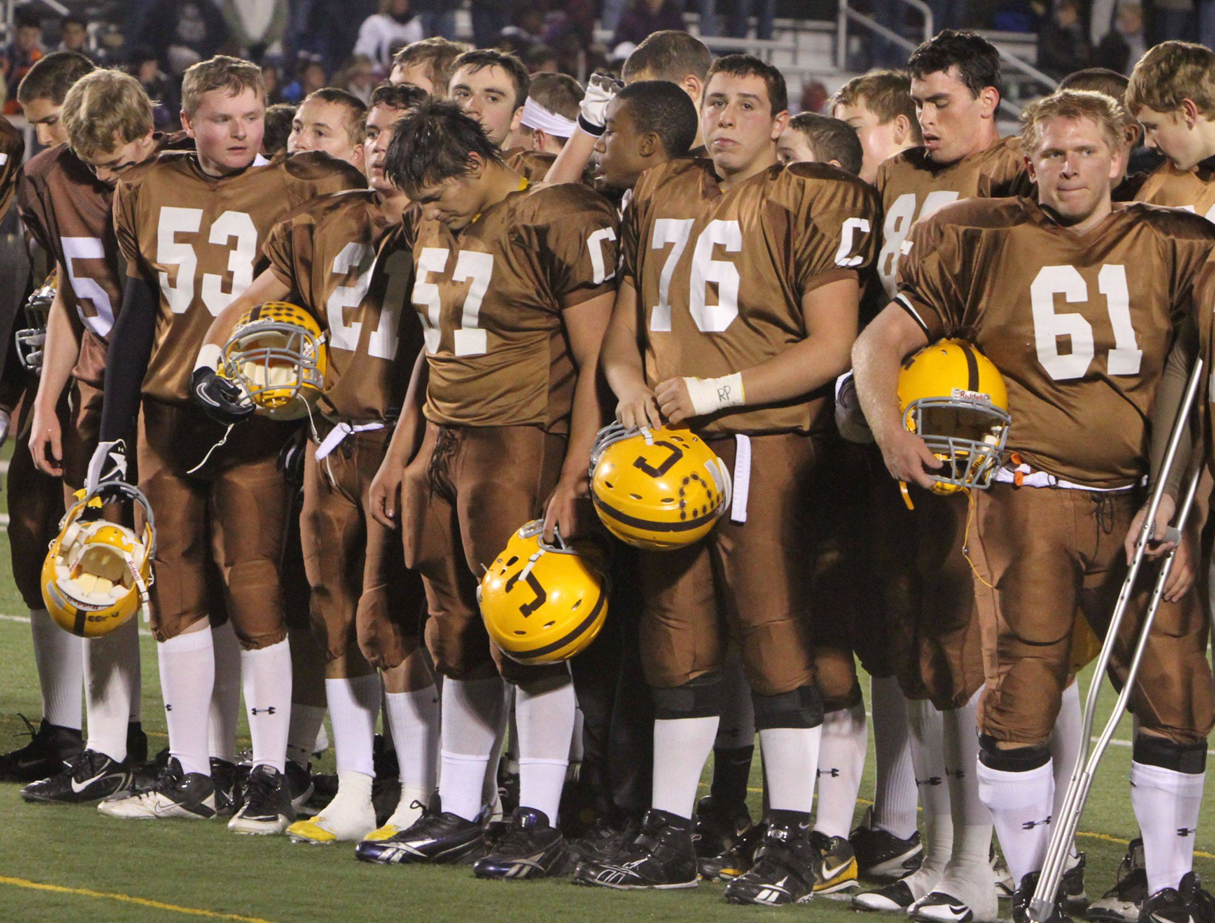 Carmel football players observe a moment of silence for Declan Sullivan, a 20-year-old junior from Long Grove, who died Wednesday at Norte Dame's practice football field, before Carmel's game with Elgin in round one of Class 7A state playoffs at Carmel in Mundelein on Friday, October 29.
