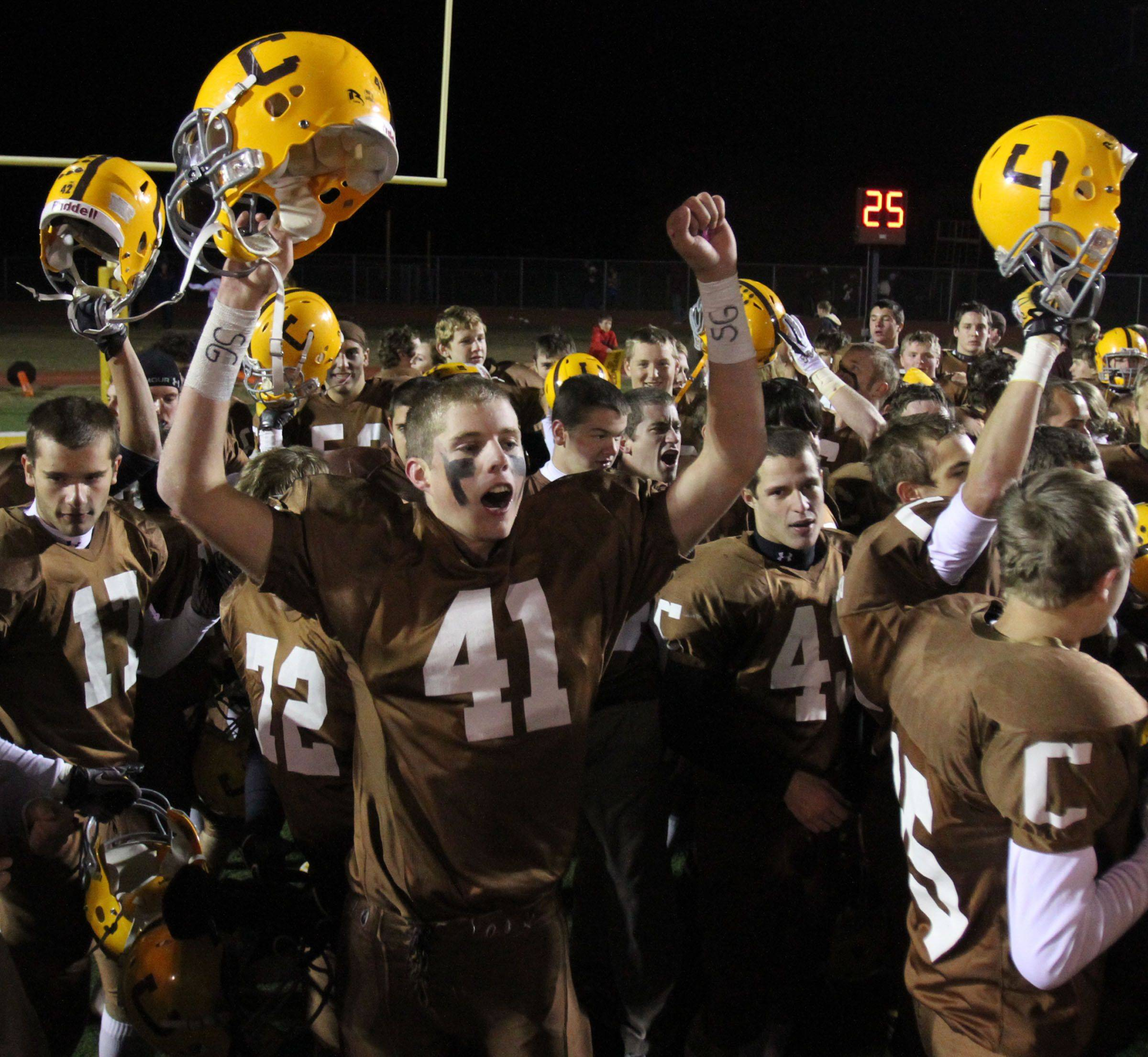Carmel's Michael Fitzgibbons and teammates celebrates winning 55-7 over Elgin in round one of Class 7A state playoffs at Carmel in Mundelein on Friday, October 29.