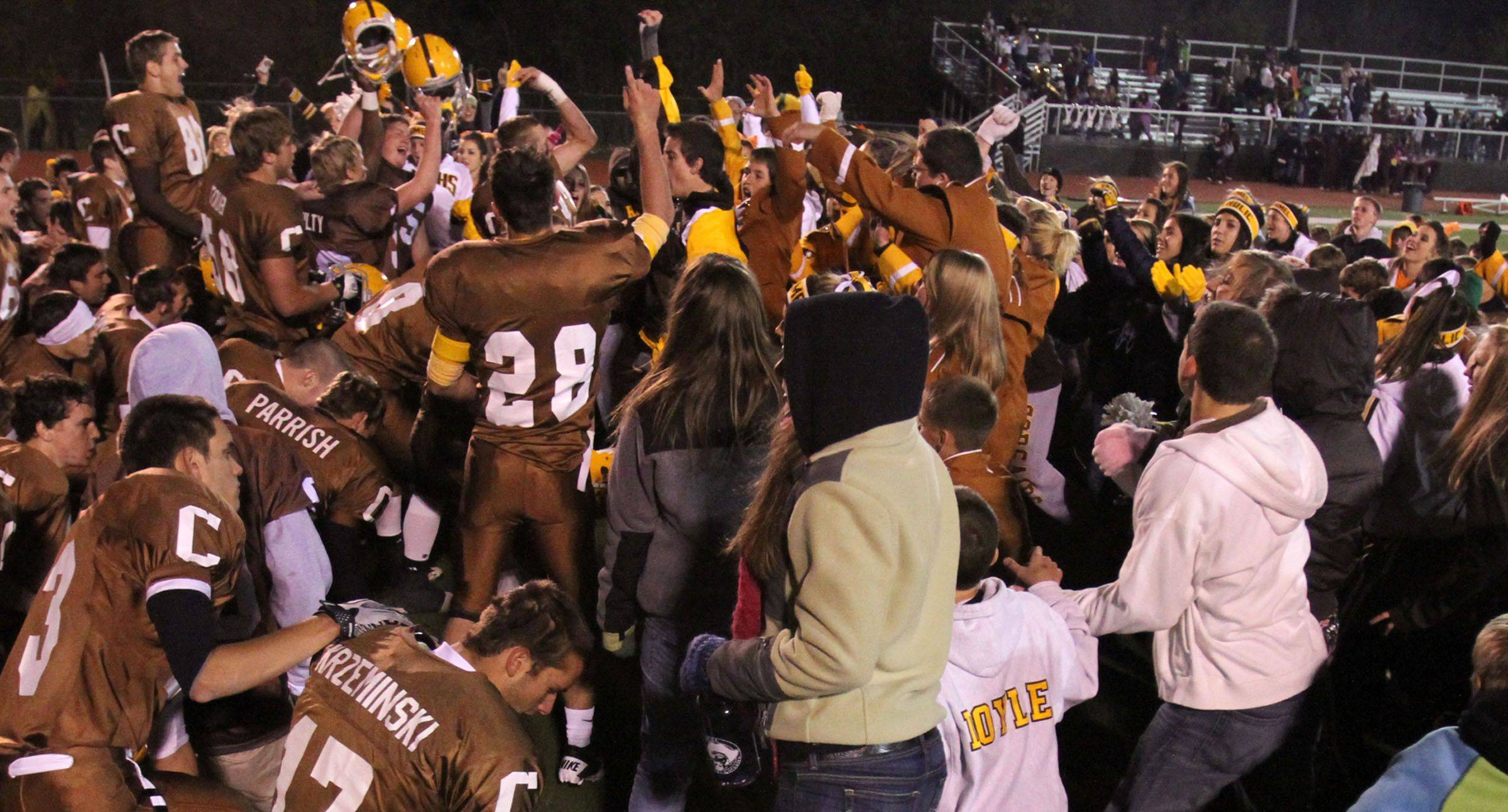 Carmel players and student fans celebrates winning 55-7 over Elgin in round one of Class 7A state playoffs at Carmel in Mundelein on Friday, October 29.