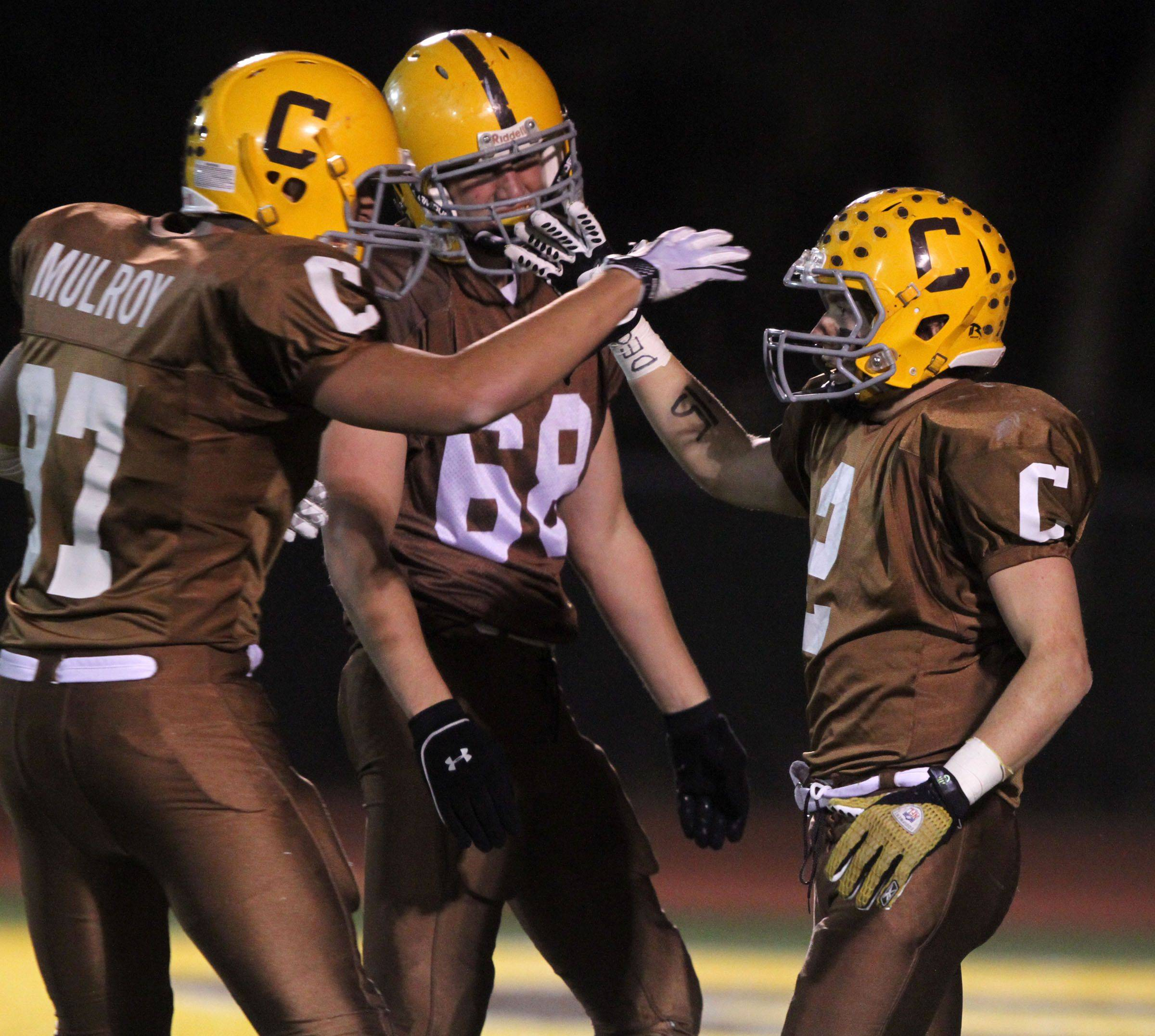 Carmel's Patrick Mulroy, left to right, and Jack Butler celebrate a touchdown by Brian Brennam in round one of Class 7A state playoffs at Carmel in Mundelein on Friday, October 29.