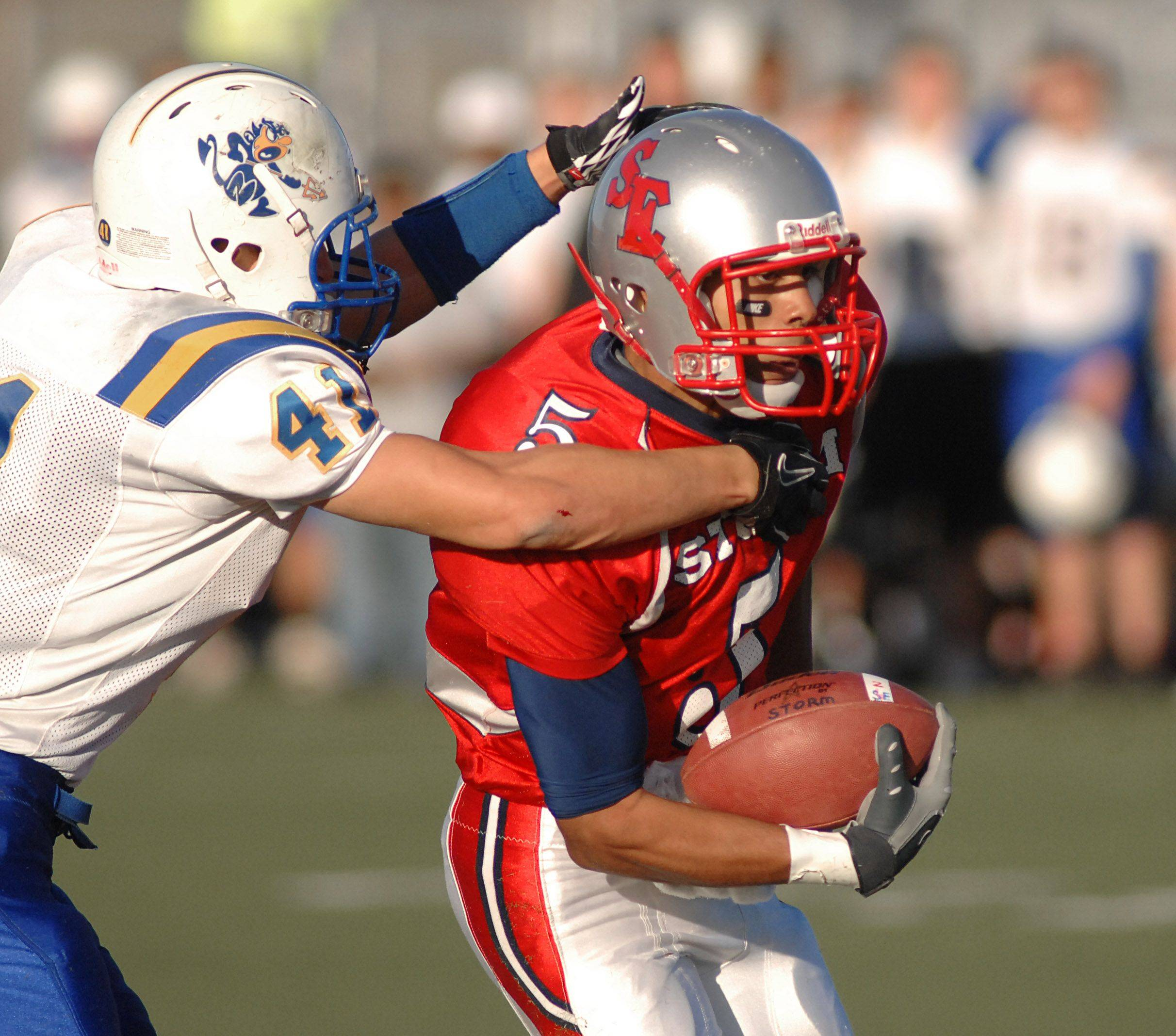 South Elgin's Domico Failla is wrapped up by Warren's Matt Goad .