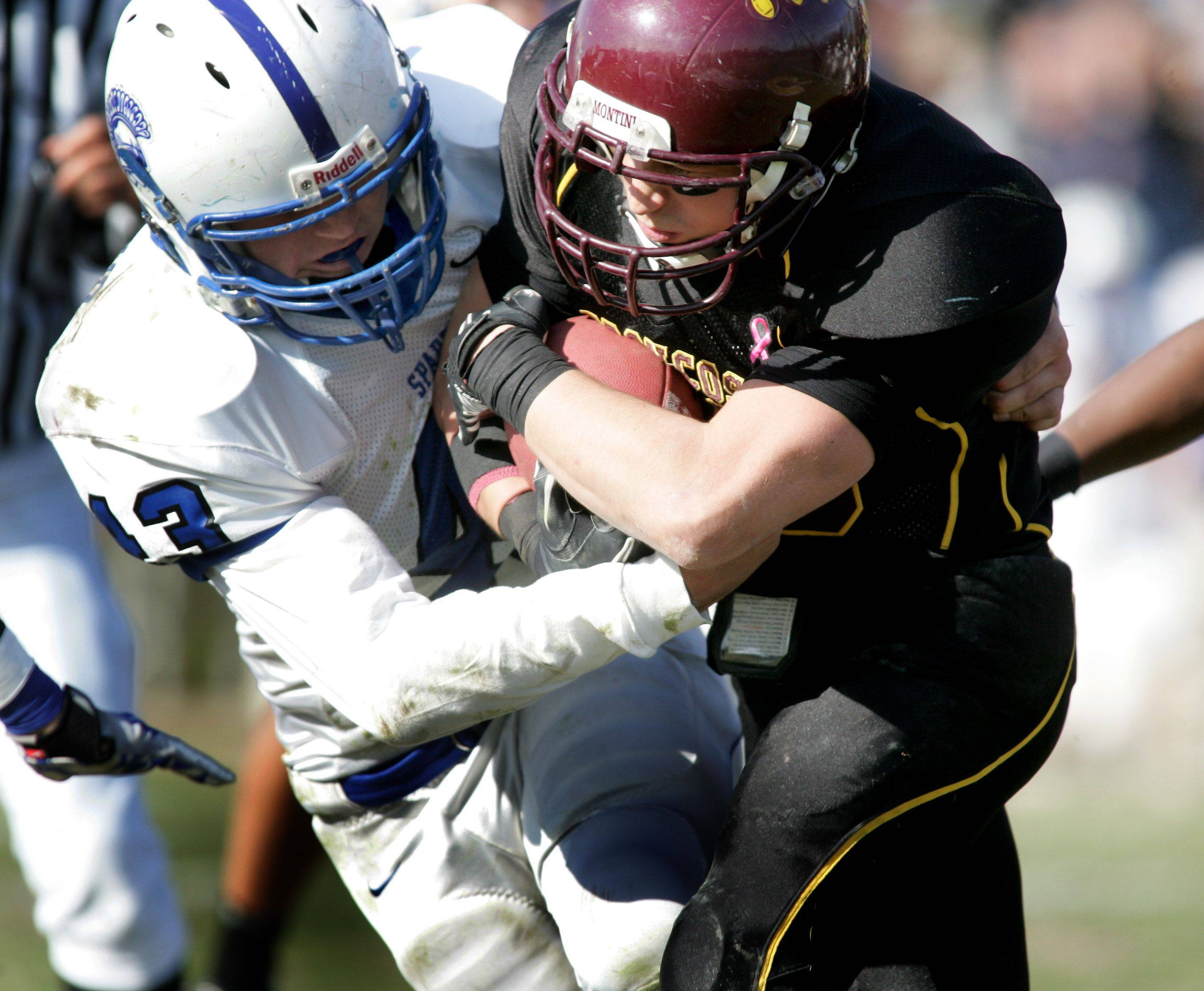 Jack Petrando of St. Francis, left, moves in to tackle Frank Baer of Montini, right.