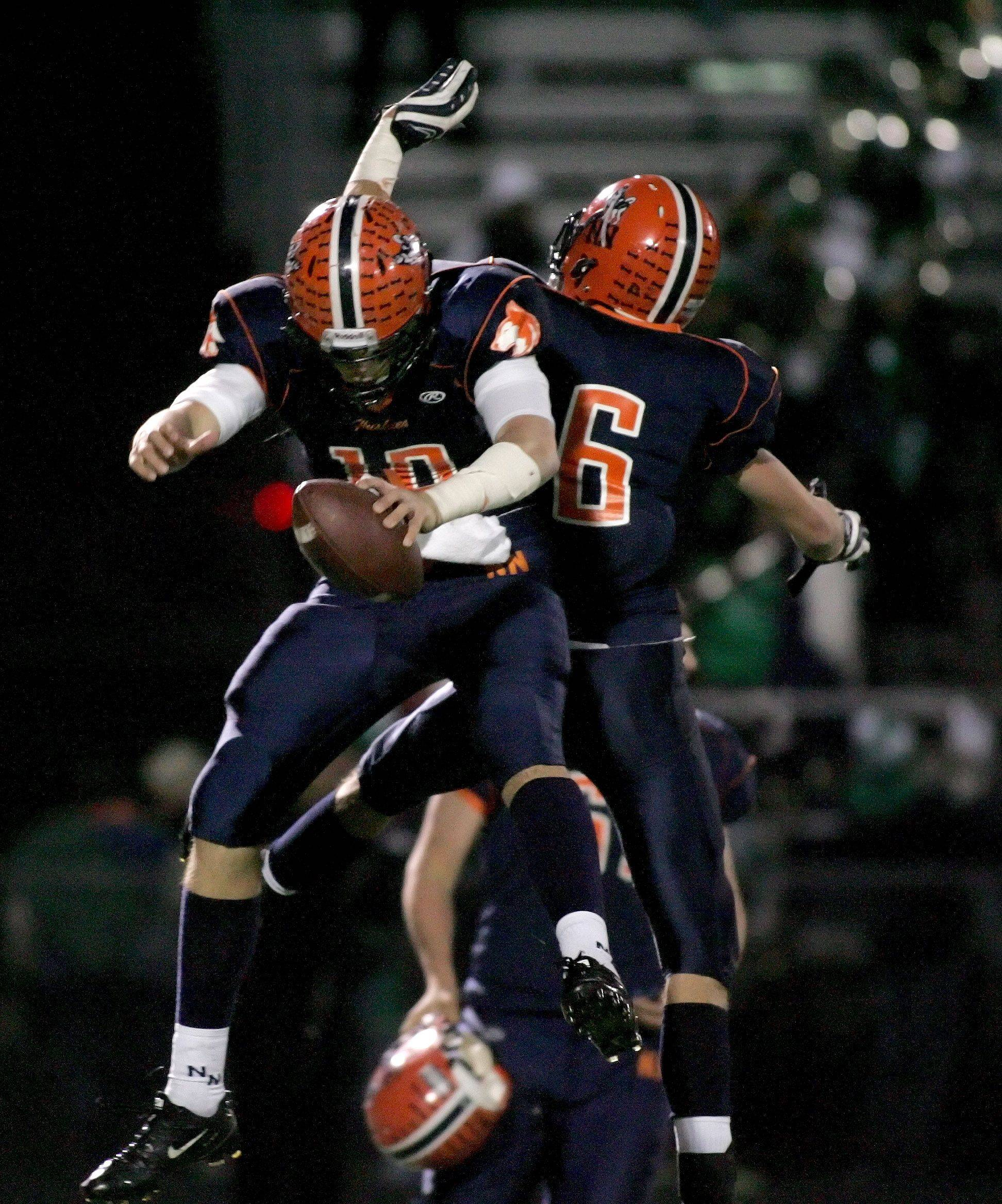 Naperville North quarterback Matt Lacosse, left and Ryan Kelsey jump up to celebrate after their win over York.