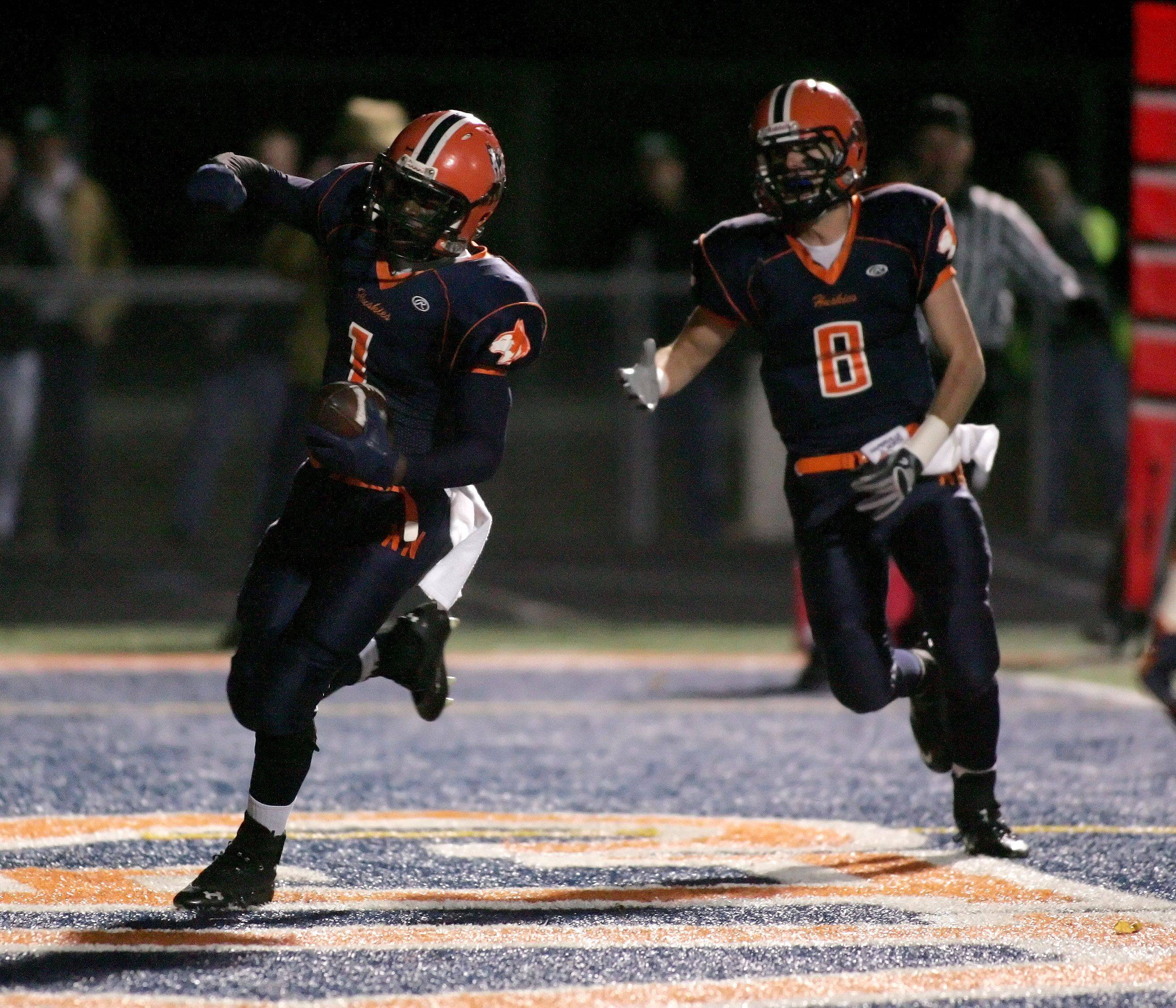 Antonio Owens of Naperville North, left comes into the end zone for a touchdown, with Craig Montgomery, right.