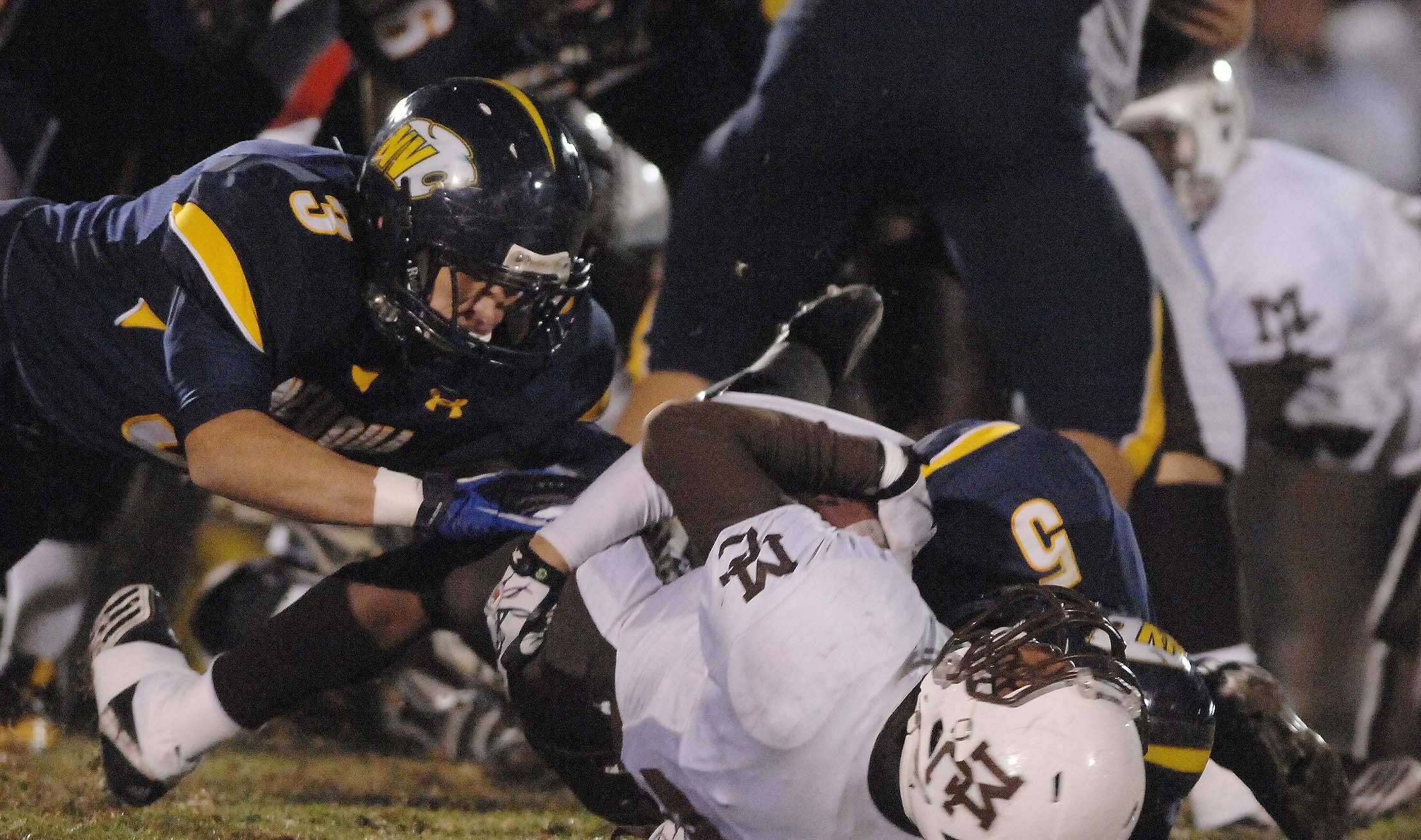 Dillon Strack ,left, and TJ Rhattigan of Neuqua Valley bring down Michael Banks of Mt. Carmel .