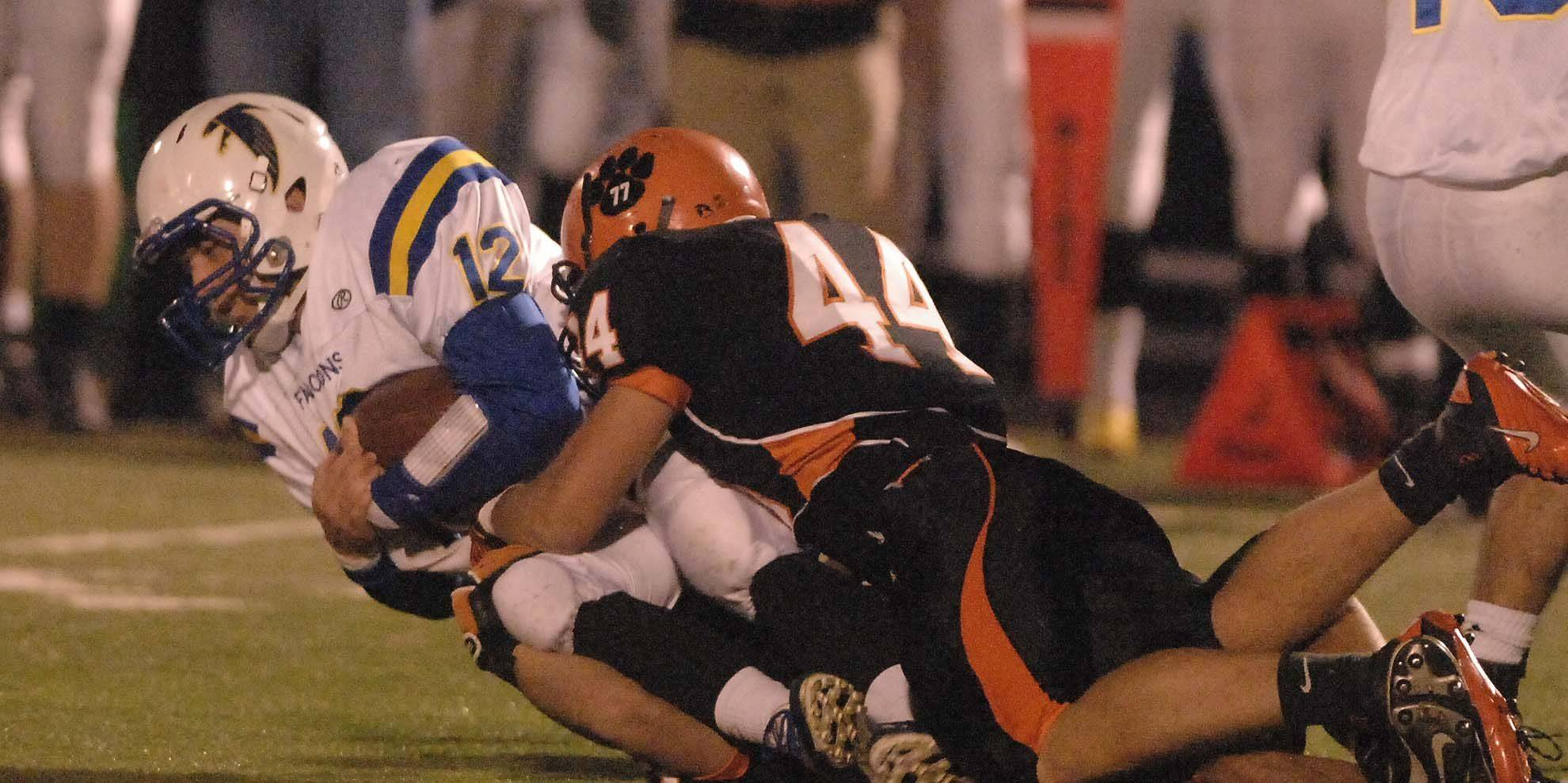 Reece Butler of Wheaton North,left, is pulled down by Brandon Peterson of Wheaton Warrenville South during the Wheaton North at Wheaton Warrenville South game Saturday.