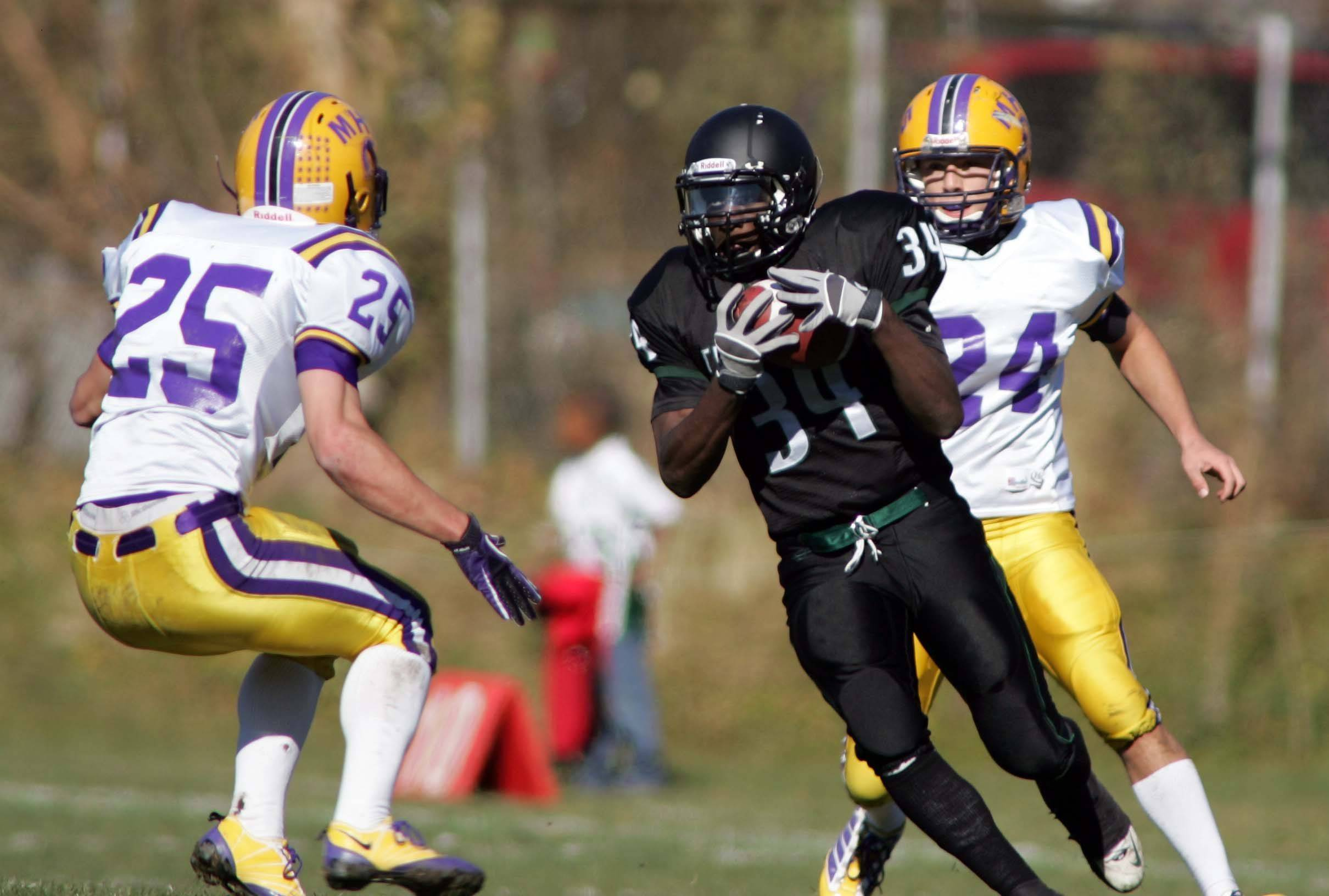 St. Edward's DeVontae, 34, works up field past Mendota's Evan Carroll, 25, to set up a touchdown during the first quarter of Mendota at St. Edward Class 4A playoff football in Elgin Saturday, November 6, 2010.