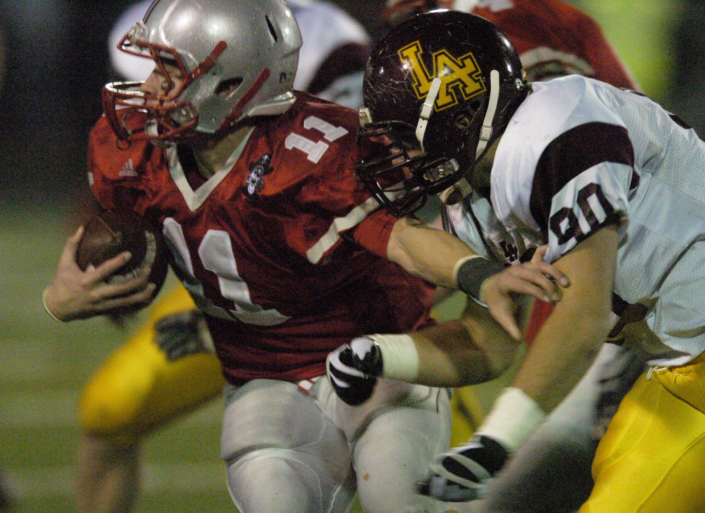 Palatine's Cody Bobbit tries to break free from Loyola Academy's Eric Hauser.