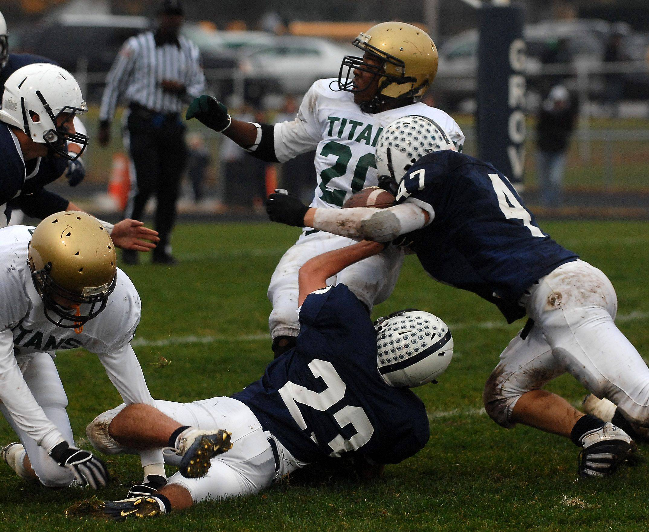 Cary-Grove's Max Kersten (47) causes a fumble by Rockford Boylan's Tyreis Thomas that was recovered by the Trojans during Saturday's playoff game in Cary.