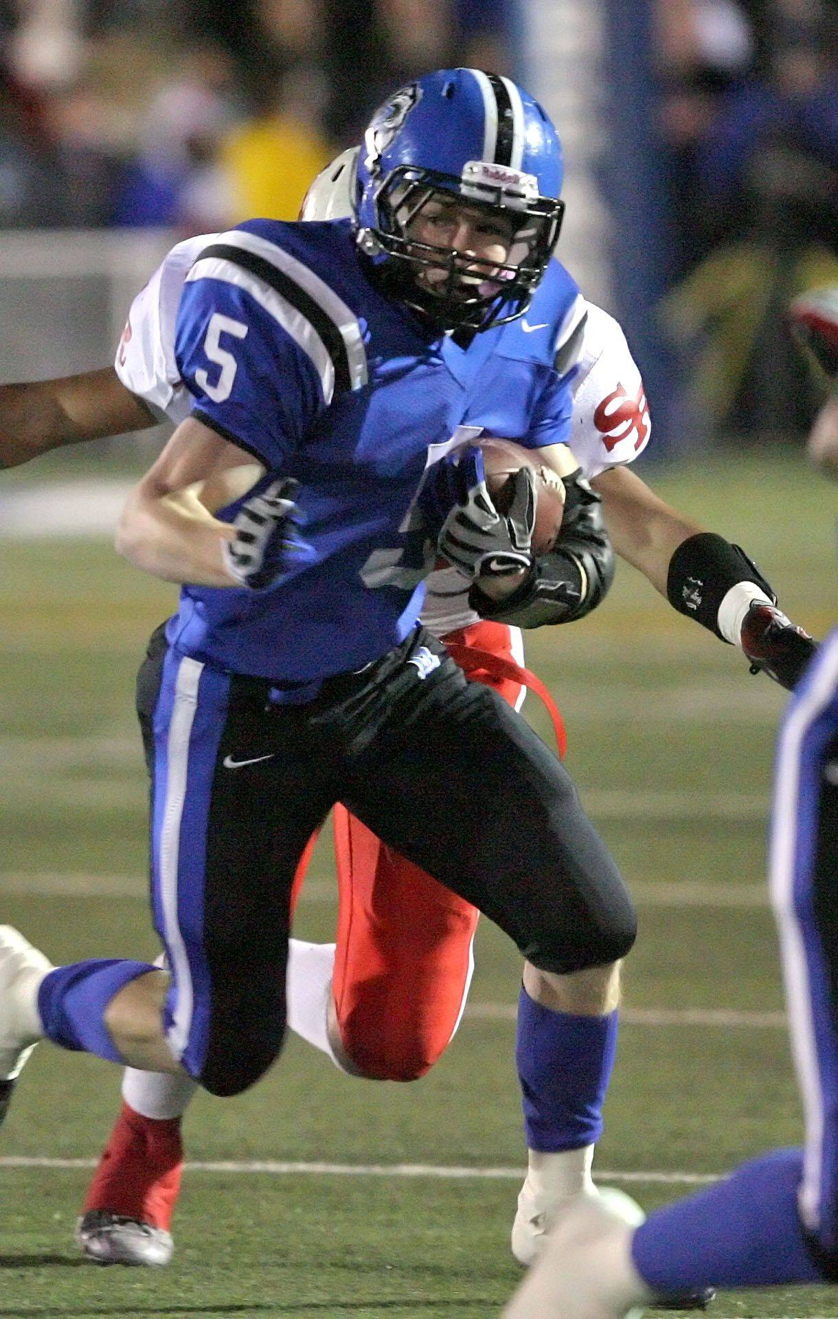 Lake Zurich's Jacob Brinlee runs during the IHSA Class 7A football semi final game against St. Rita Saturday night at Lake Zurich High School.