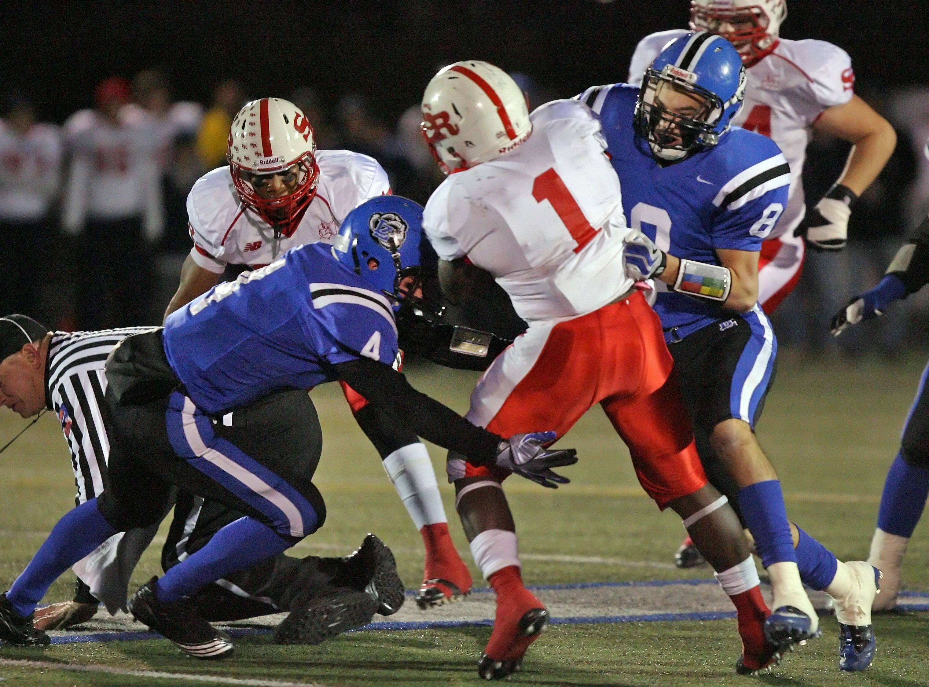 Lake Zurich's Zach Till and Chris Rantis tackle St. Rita's Jahwon Akul during the IHSA Class 7A football semi final game Saturday night at Lake Zurich High School.