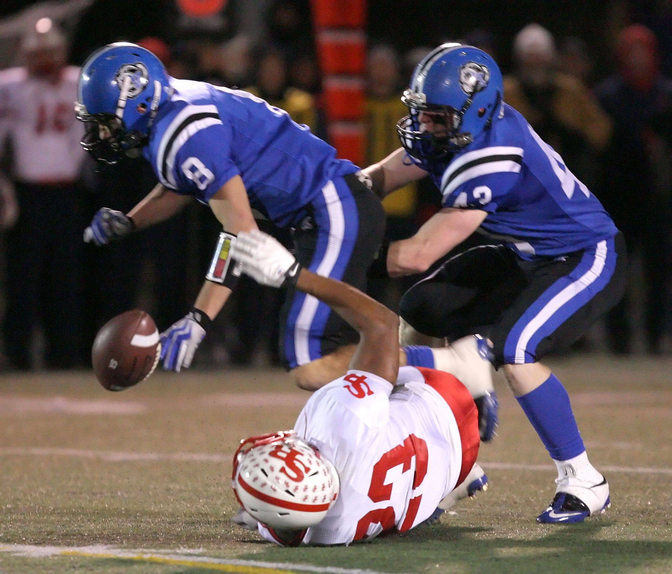 Lake Zurich'sChris Rantis and Taylor Coleman break up a pass to St. Rita's Mitch Saffold during the IHSA Class 7A football semi final game Saturday night at Lake Zurich High School.