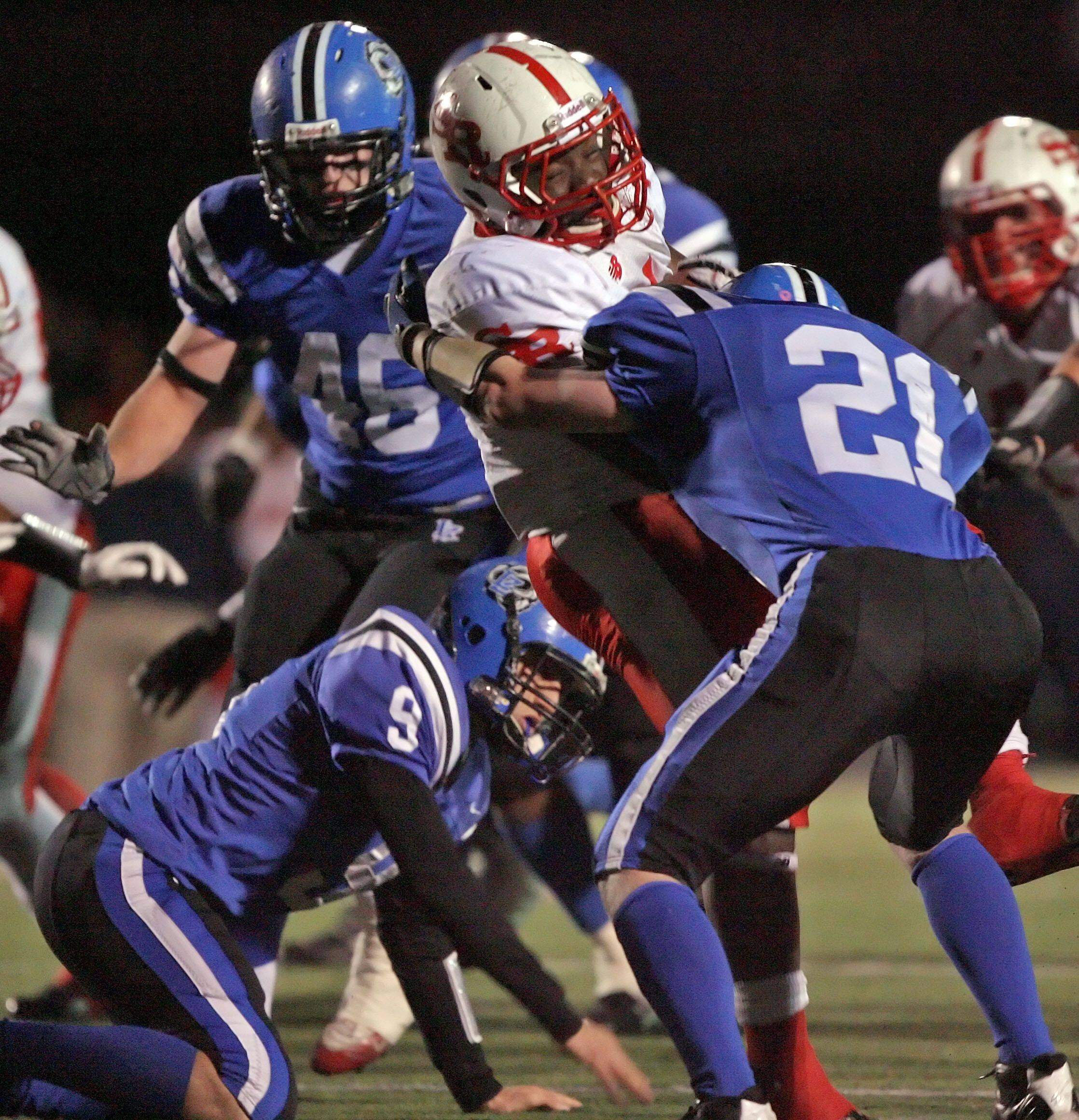 Lake Zurich's Bobby Rogers and Danny Minogue tackle St. Rita's Jahwon Akul during the IHSA Class 7A football semi final game Saturday night at Lake Zurich High School.