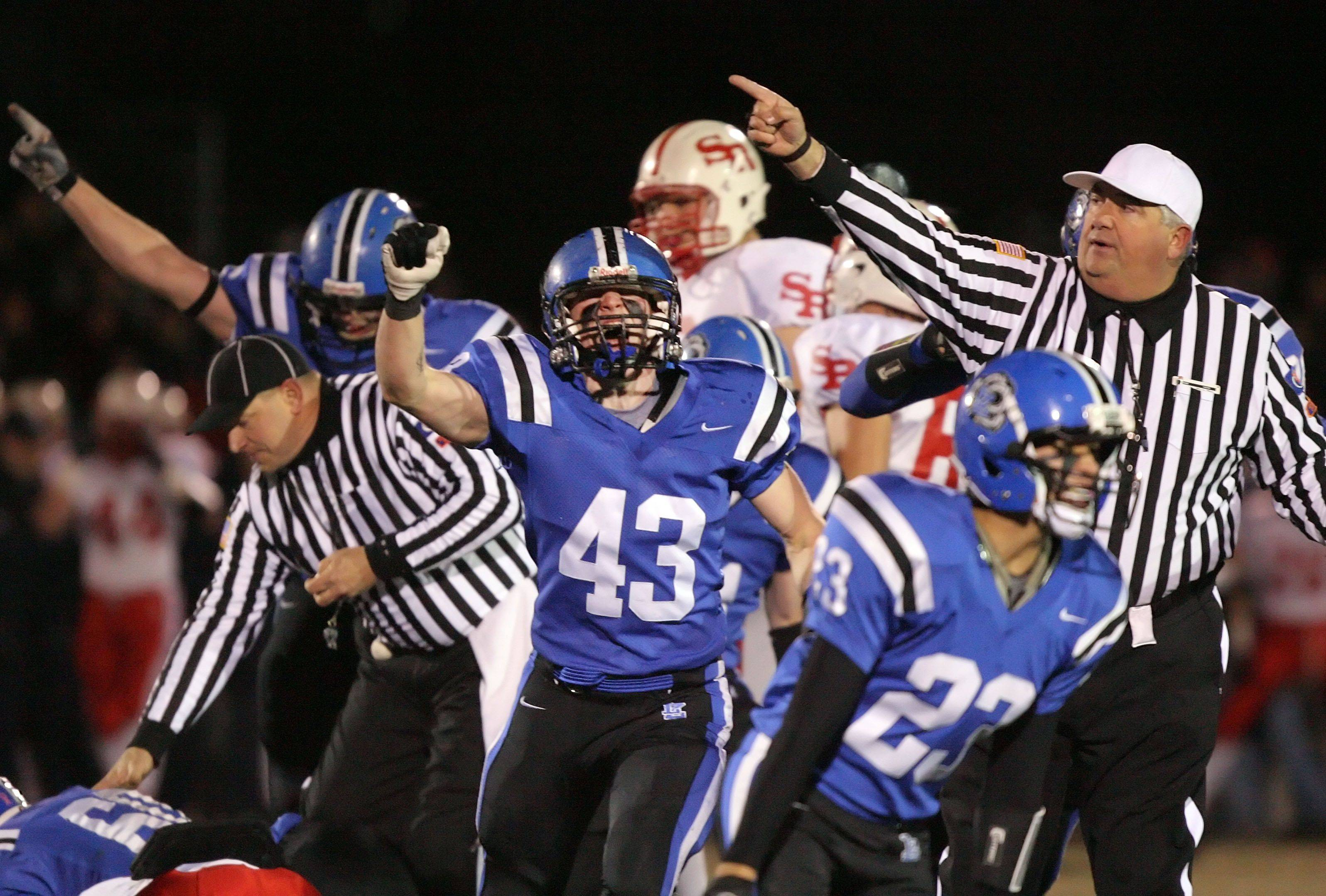 Lake Zurich's defense celebrates after recovering a St. Rita fumble during the IHSA Class 7A football semi final game Saturday night at Lake Zurich High School.