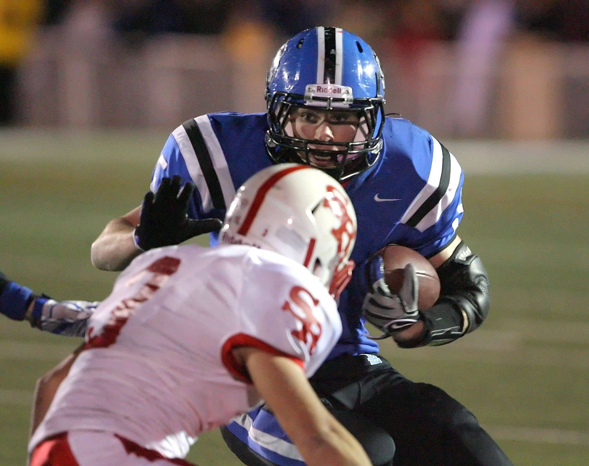 Lake Zurich's Jacob Brinlee runs towards St. Rita's Jimmy Johnson during the IHSA Class 7A football semi final game Saturday night at Lake Zurich High School.