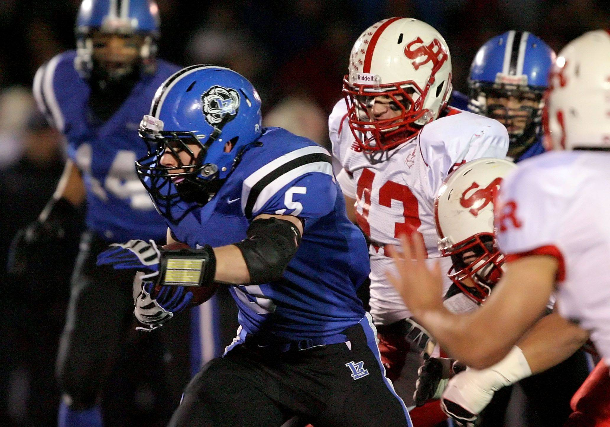 Lake Zurich's Jacob Brinlee runs by St. Rita's Matt Mullen during the IHSA Class 7A football semi final game Saturday night at Lake Zurich High School.