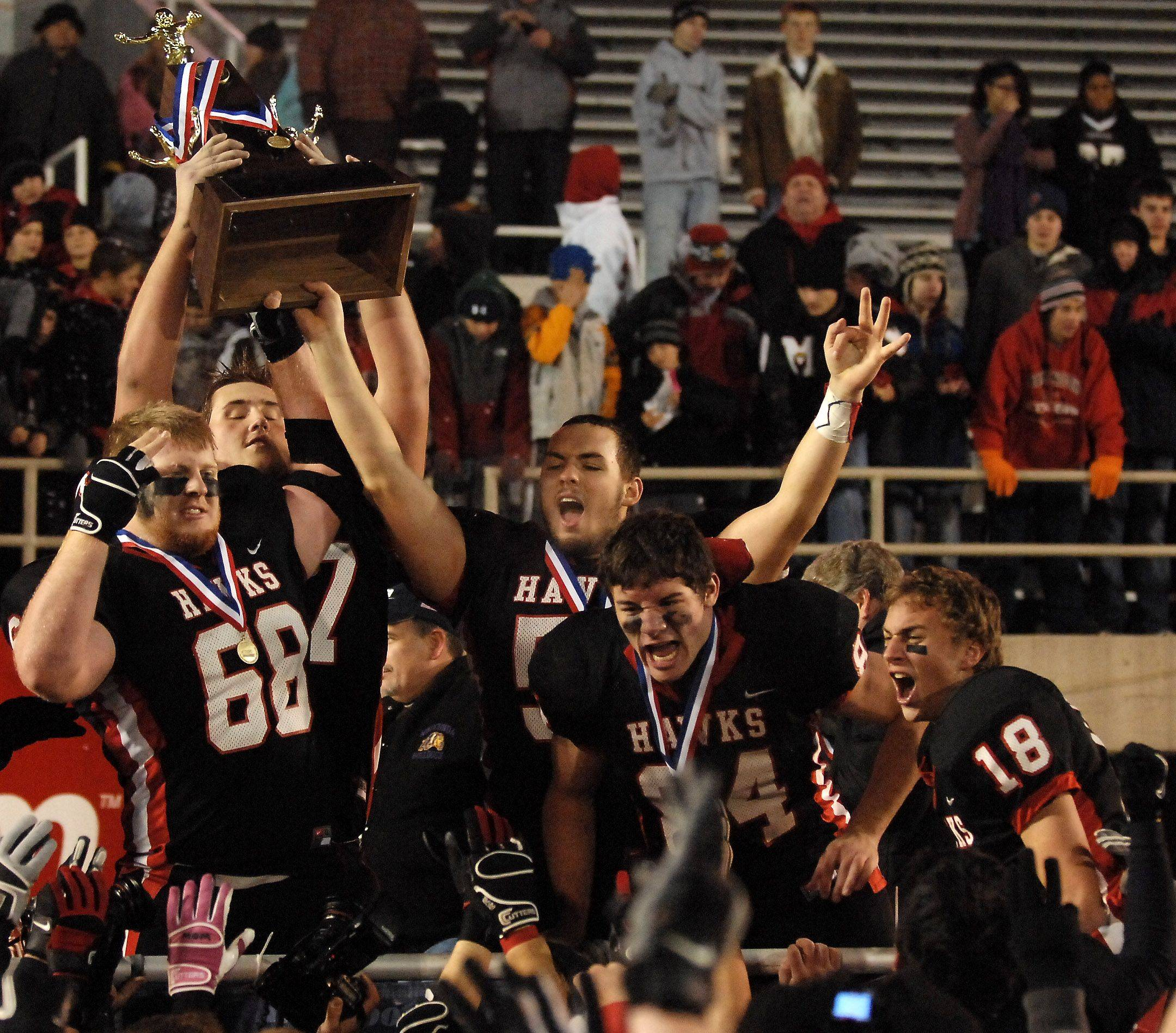 The Maine South captains hoist the championship trophy following their win over Mt. Carmel during the Class 8A state final in Champaign Saturday.