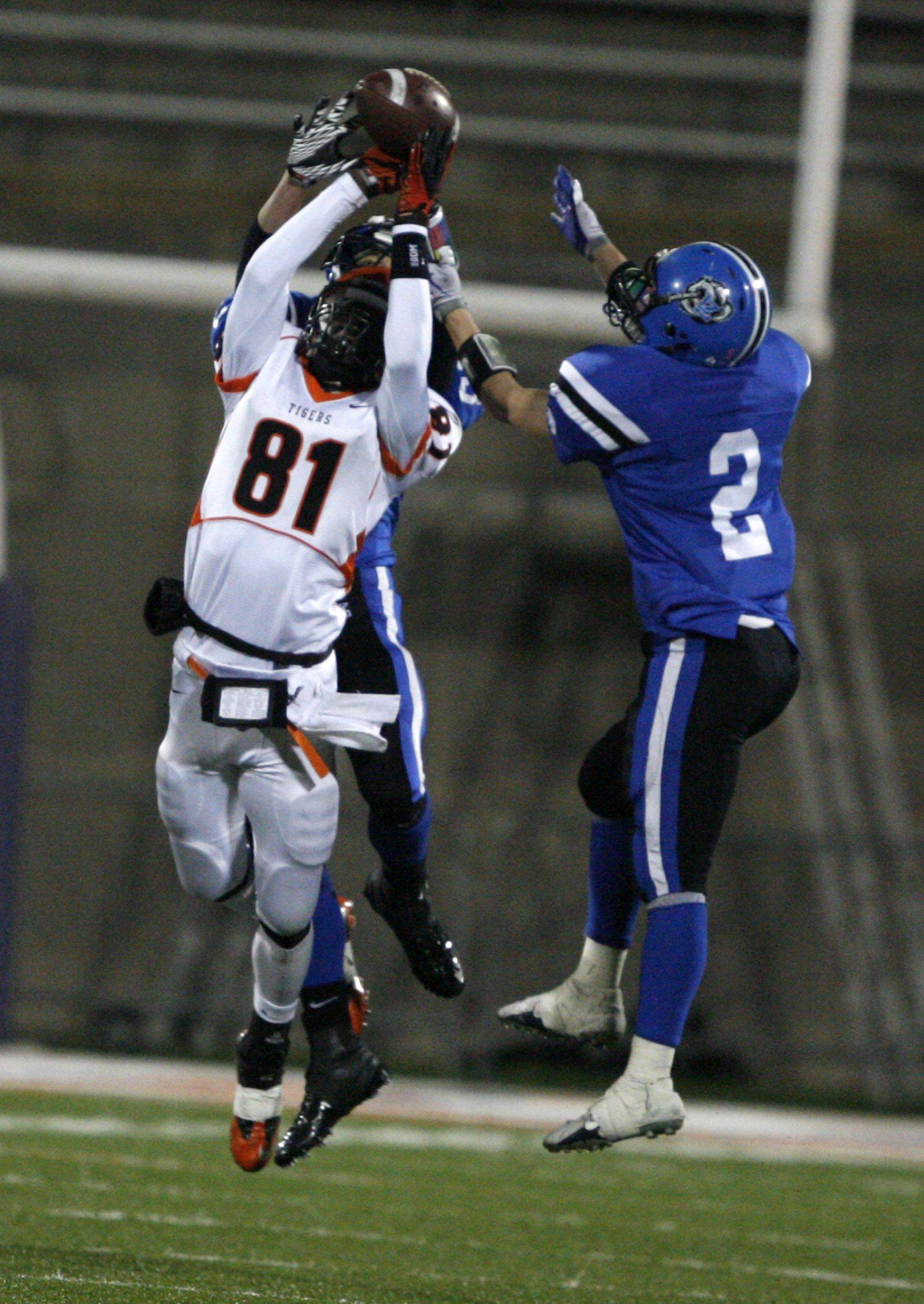Wheaton Warrenville South's Titus Davis and Lake Zurich's Mike Shield leap for an incomplete pass in the 7A state title game in Champaign on Saturday, November 27.