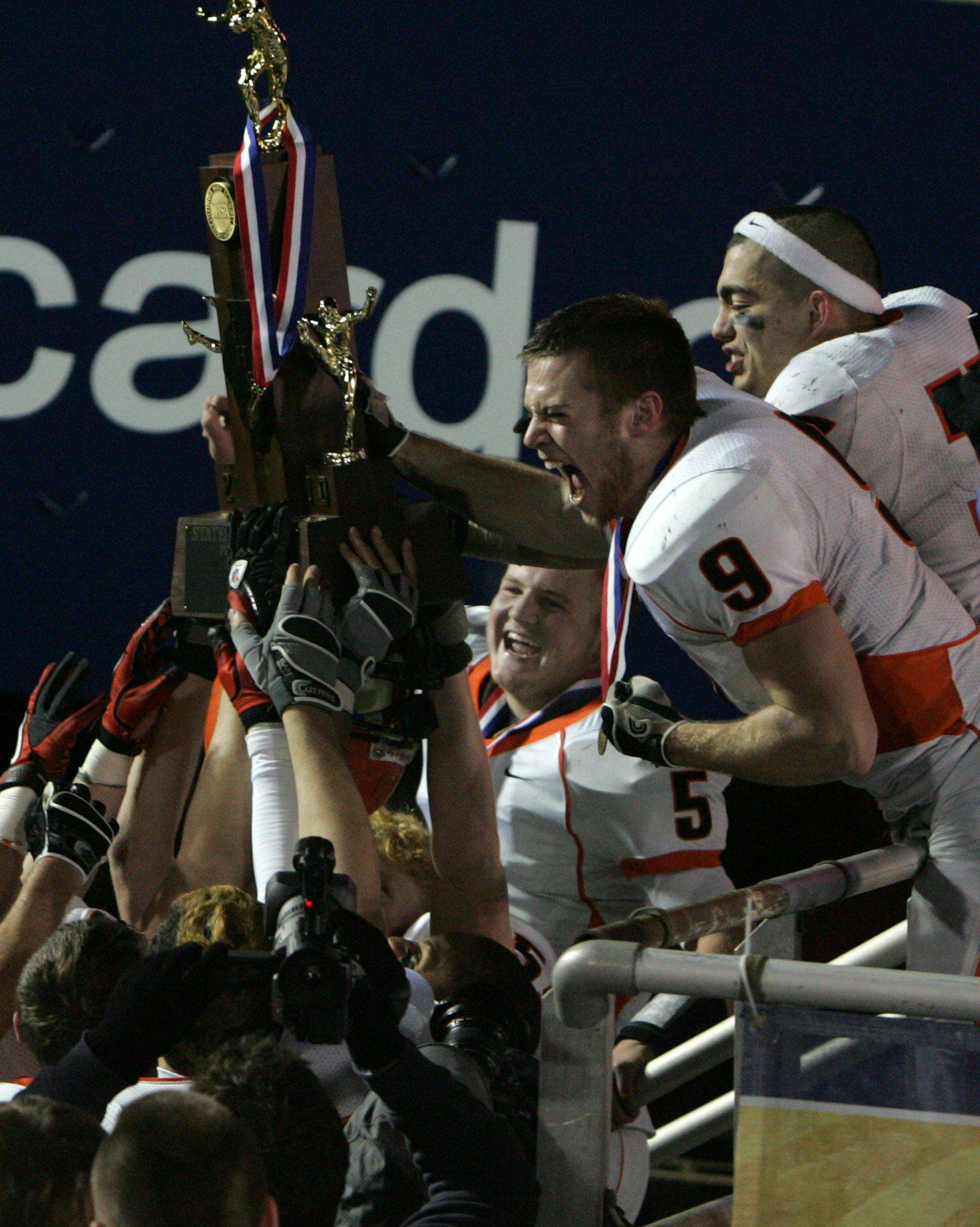 Wheaton Warrenville South's Sam Prete celebrates with the state trophy after winning 28-17 over Lake Zurich in the 7A state title game in Champaign on Saturday, November 27.