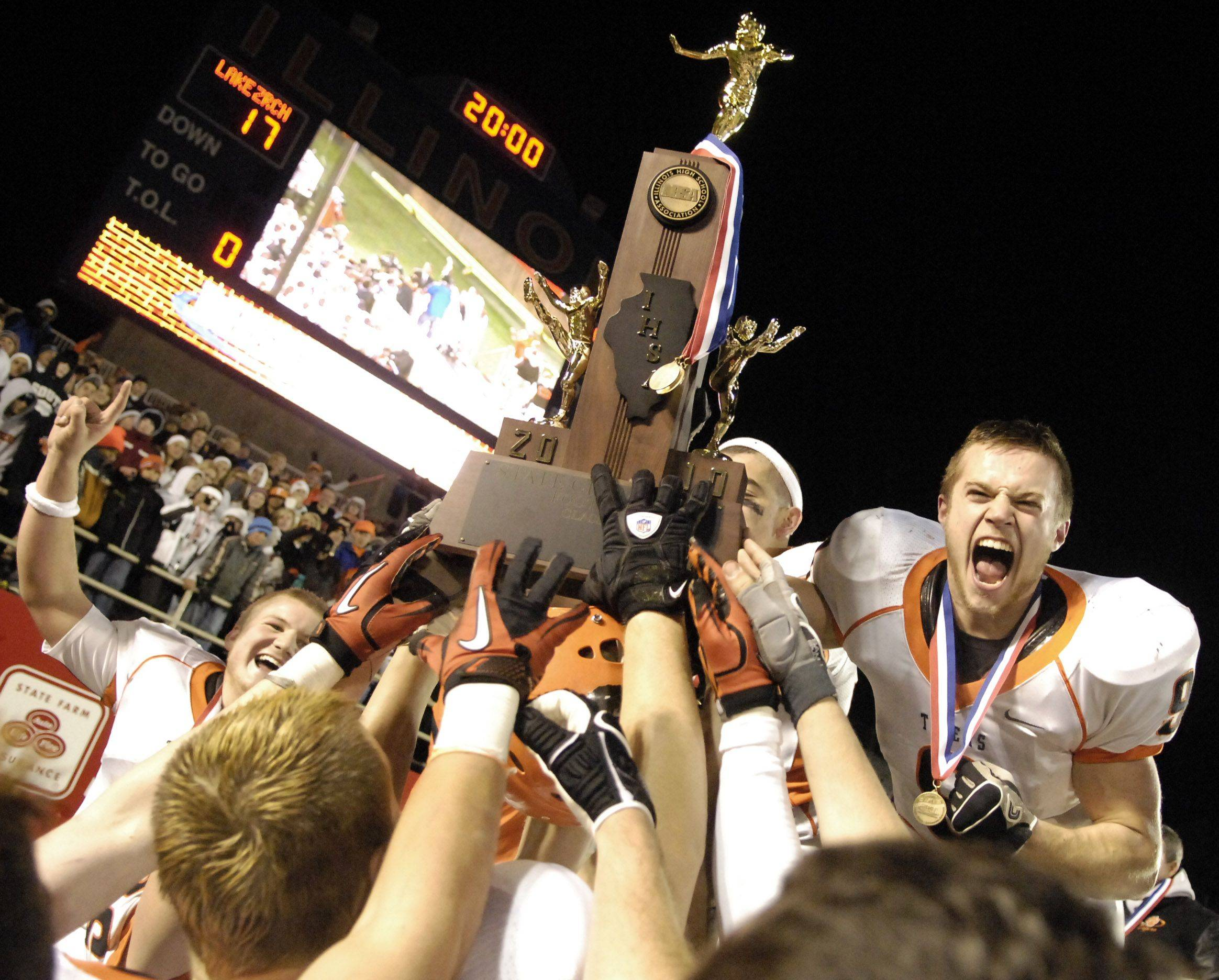 Wheaton Warrenville South's Matt Rogers (right) and his fellow captains hold up the championship trophy after beating Lake Zurich during the Class 7A state final in Champaign Saturday.