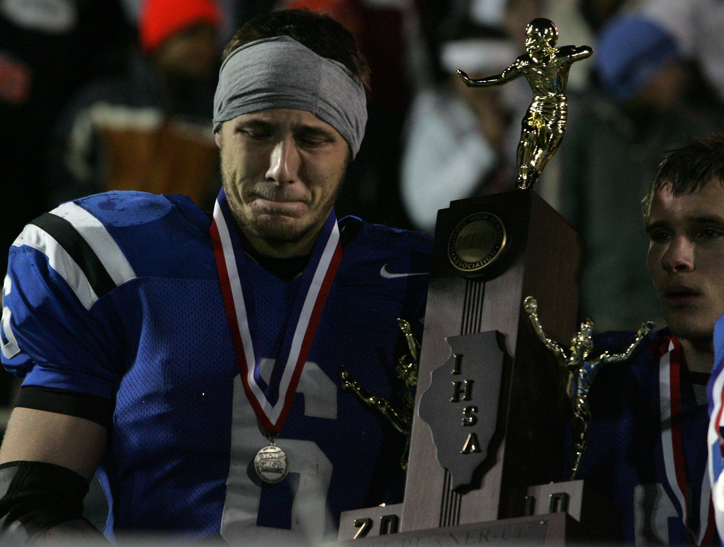 Lake Zurich's JJH Raffelson holds the place trophy after losing to Wheaton Warrenville South 28-17 in the 7A state title game in Champaign on Saturday, November 27.