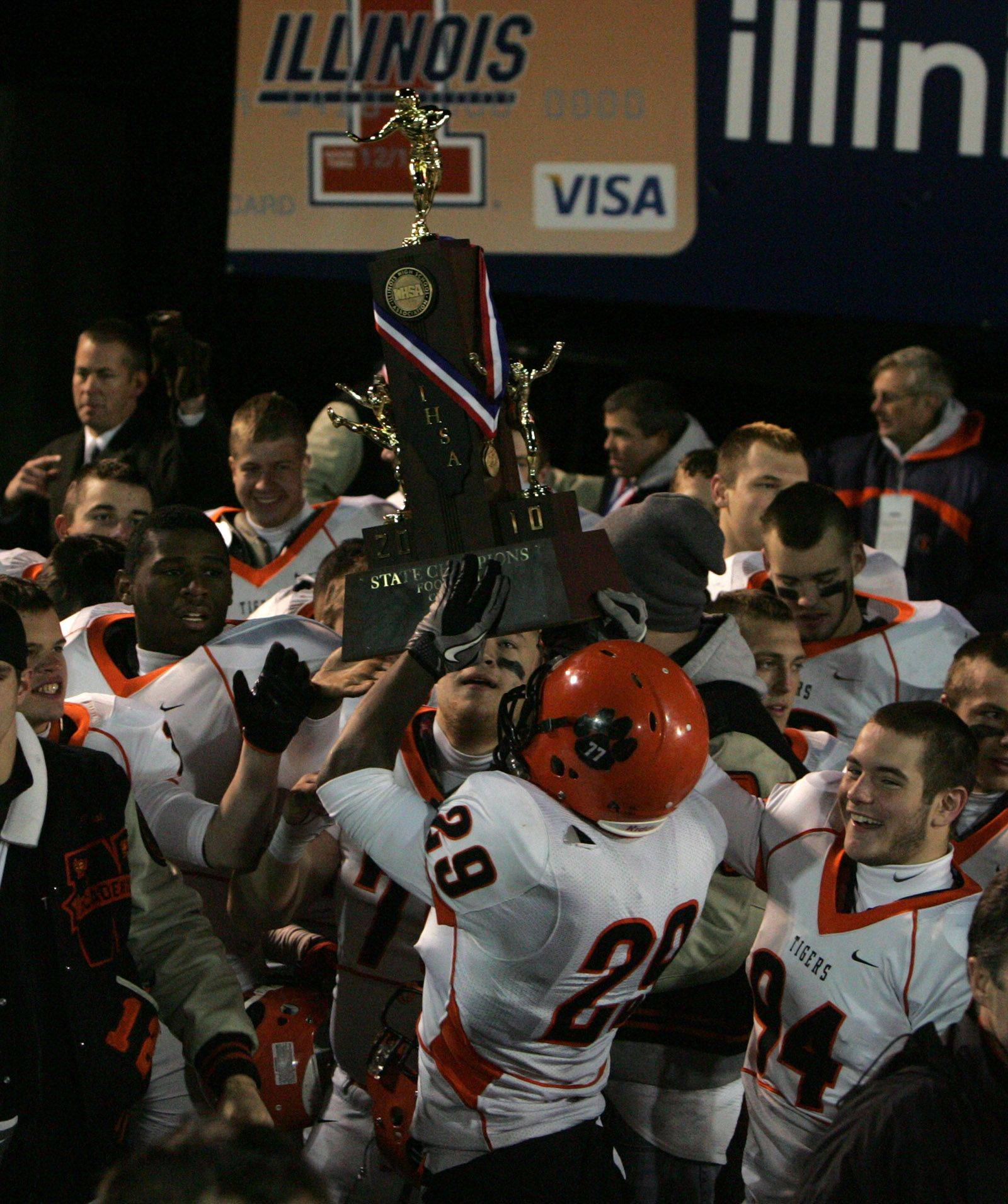 Wheaton Warrenville South celebrates with the state trophy after winning 28-17 over Lake Zurich in the 7A state title game in Champaign on Saturday, November 27.