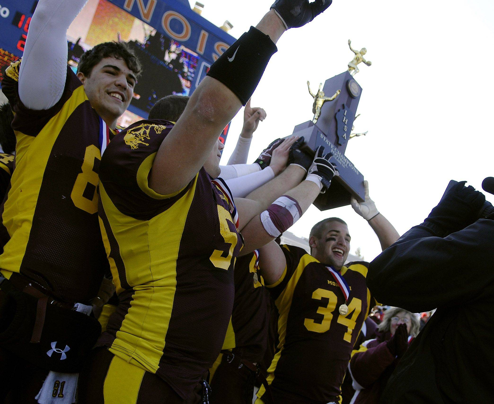 Montini's Doug Diedrick (34) and his fellow captains hoist the championship trophy after beating Chatham Glenwood during the Class 5A state championsip in Champaign Saturday.