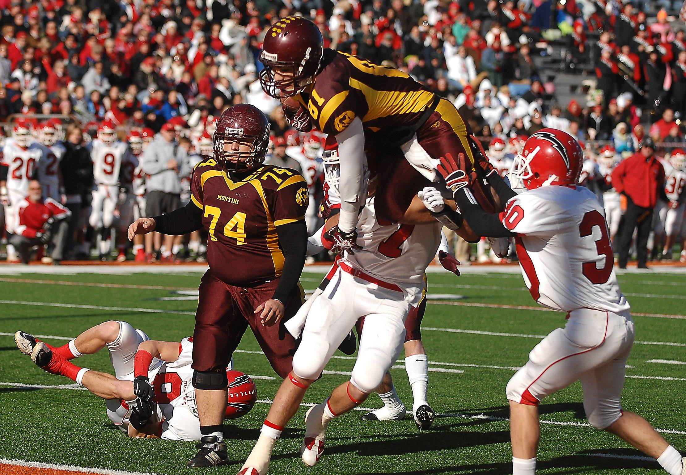 Montini's Jordan Westerkamp leaps over two Chatham Glenwood defenders to score his first touchdown during the Class 5A state championsip in Champaign Saturday.