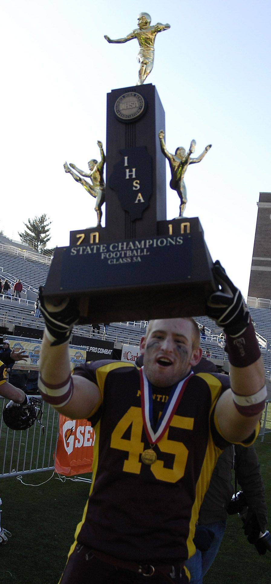 Montini's Alex Walters hoists the trophy following the Class 5A state championsip in Champaign Saturday.
