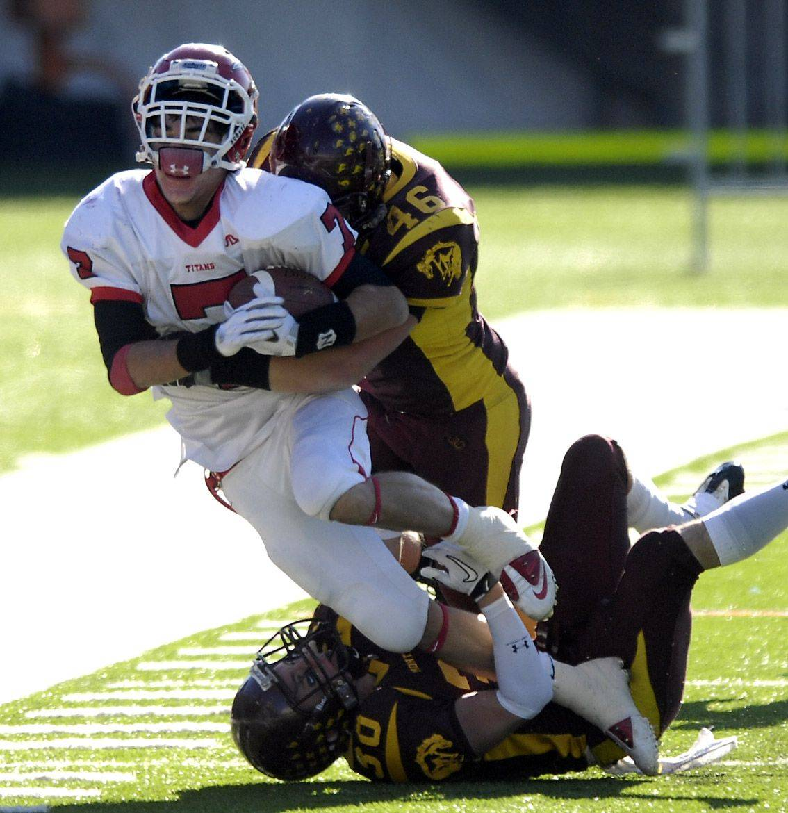 Montini's Frank Bruscianelli (46) and Mike Kaiser combine to lay out Chatham Glenwood's Tony Giovannelli during the Class 5A state championsip in Champaign Saturday.
